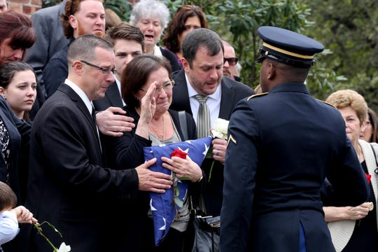 Jill Gado, wife of retired New Rochelle police detective Mark Gado, salutes a military officer after being presented with the American flag that draped her husband's coffin after Gado's funeral at the Church of St. Denis in Hopewell Junction Sept. 22, 2018. Gado, a resident of Hopewell Junction, who spent days at the World Trade Center after the Sept. 11 attacks, died of 9/11 related illness. With Jill Gado were her sons Mark, left, and Chris.