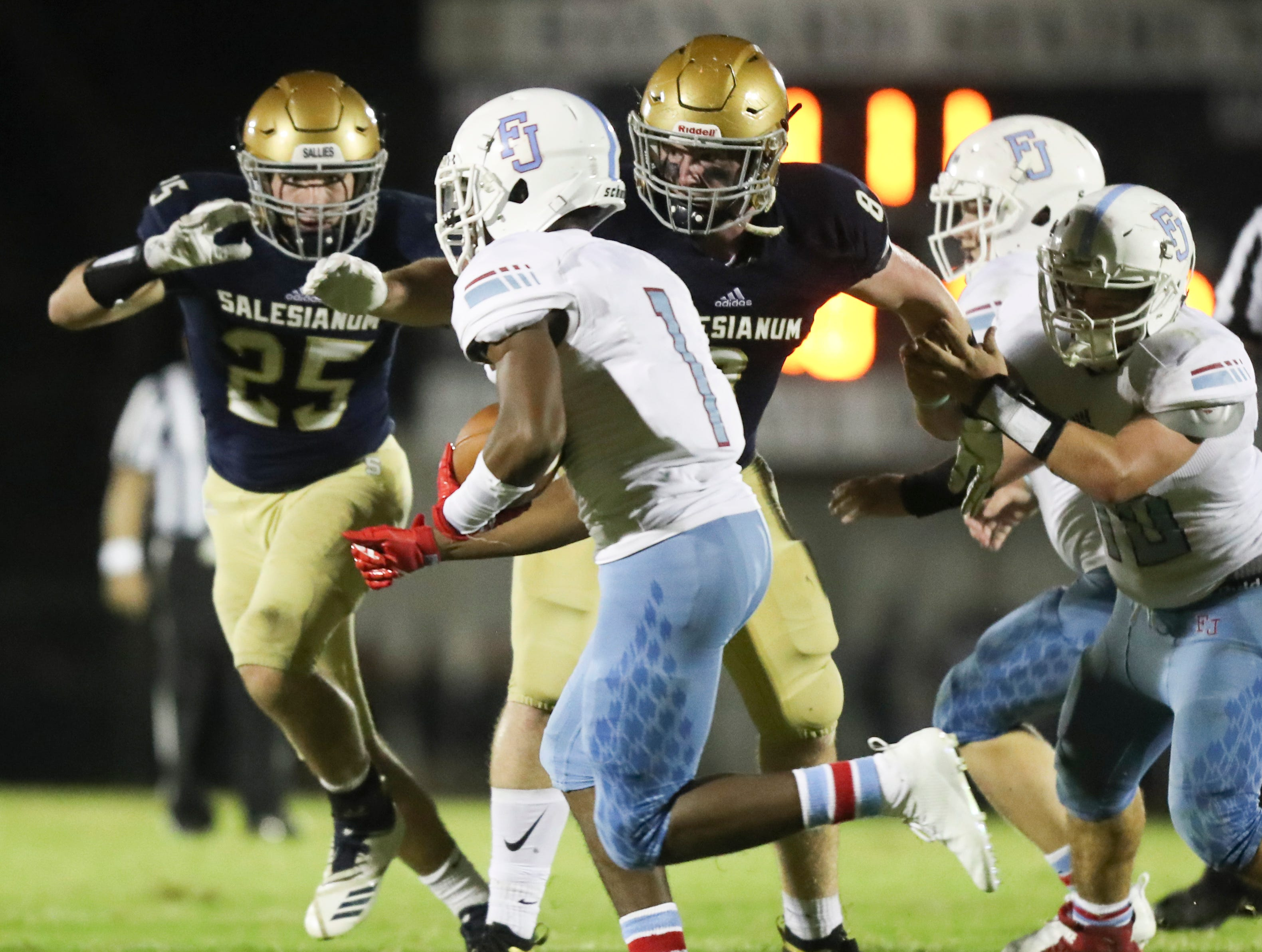 Salesianum's Colin Fowler (left) and Logan Bushweller move for Father Judge ball carrier Dameir Johnson in the second half of Salesianum's 21-14 win at Baynard Stadium Friday.