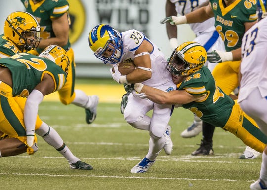 Delaware running back DeJoun Lee is wrapped up by North Dakota State linebacker Dan Marlette