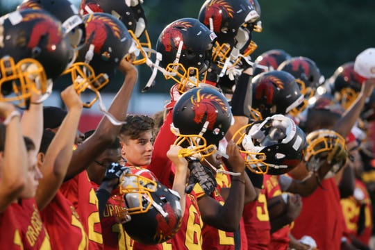 Glasgow players hold their helmets up at the end of the national anthem before the Dragons' 41-20 loss to Brandywine on Sept. 21, 2018.