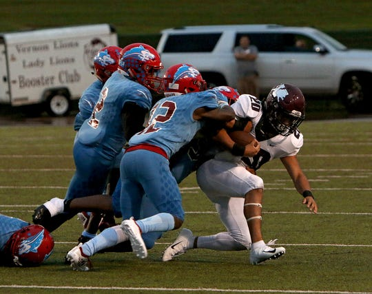 Vernon's Christian Ochoa (20) is stopped by a group of Hirschi defenders on Friday, Sept. 21, 2018, at Memorial Stadium.