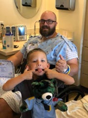 "Wichita Falls police officer Tim Putney gets a present from an admirer, Cason Edwards, 5, on Sept. 19 in a Dallas-Fort Worth hospital. The 5-year-old made Tim a camo bear dressed in police gear at a Build-A-Bear Workshop and named it ""Police Officer Mr. Tim,"" Cason's mother, Jessica Edwards, wrote in a Facebook post.  Putney underwent two back surgeries -- the second one unexpected -- last week."