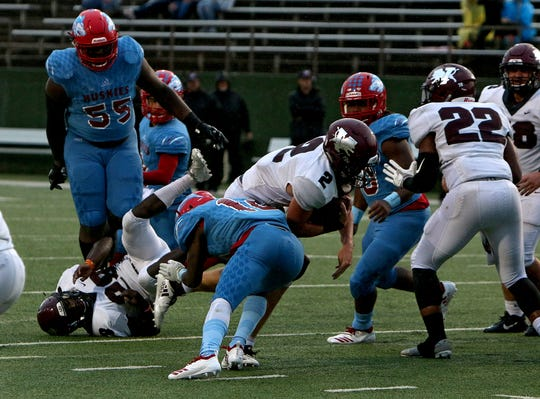 Vernon's B.T. White (2) is slowed down on a rush attempt by Hirschi's Efrain De La Paz (10) Friday, Sept. 21, 2018, at Memorial Stadium.