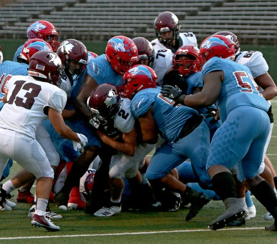 Vernon's B.T. White (2) fights for extra yardage with help from teammates as a group of Hirschi defenders Friday night.