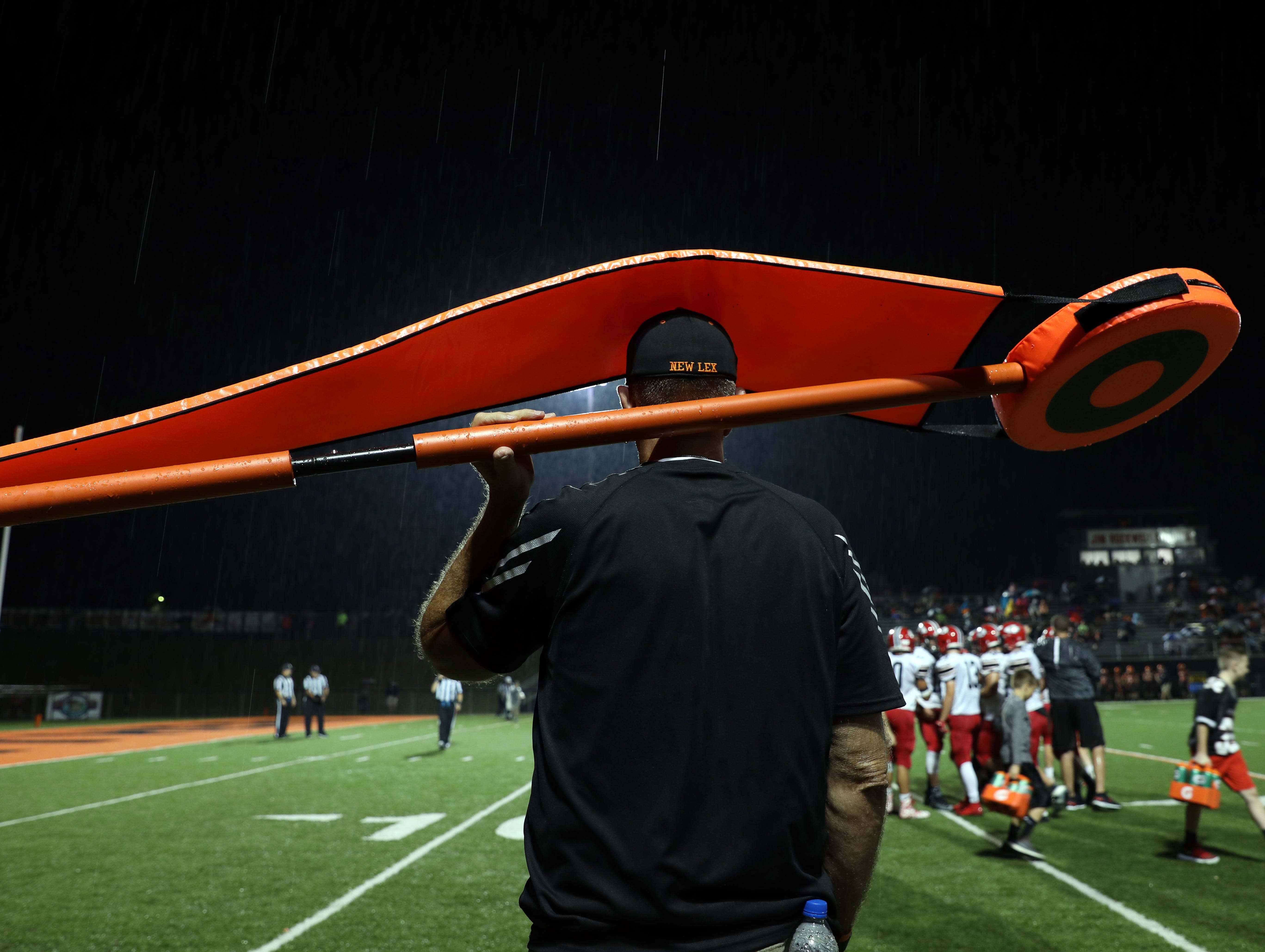 A member of the chain gang stays dry during a rainy spell in the second quarter of New Lexington's game against Coshocton.