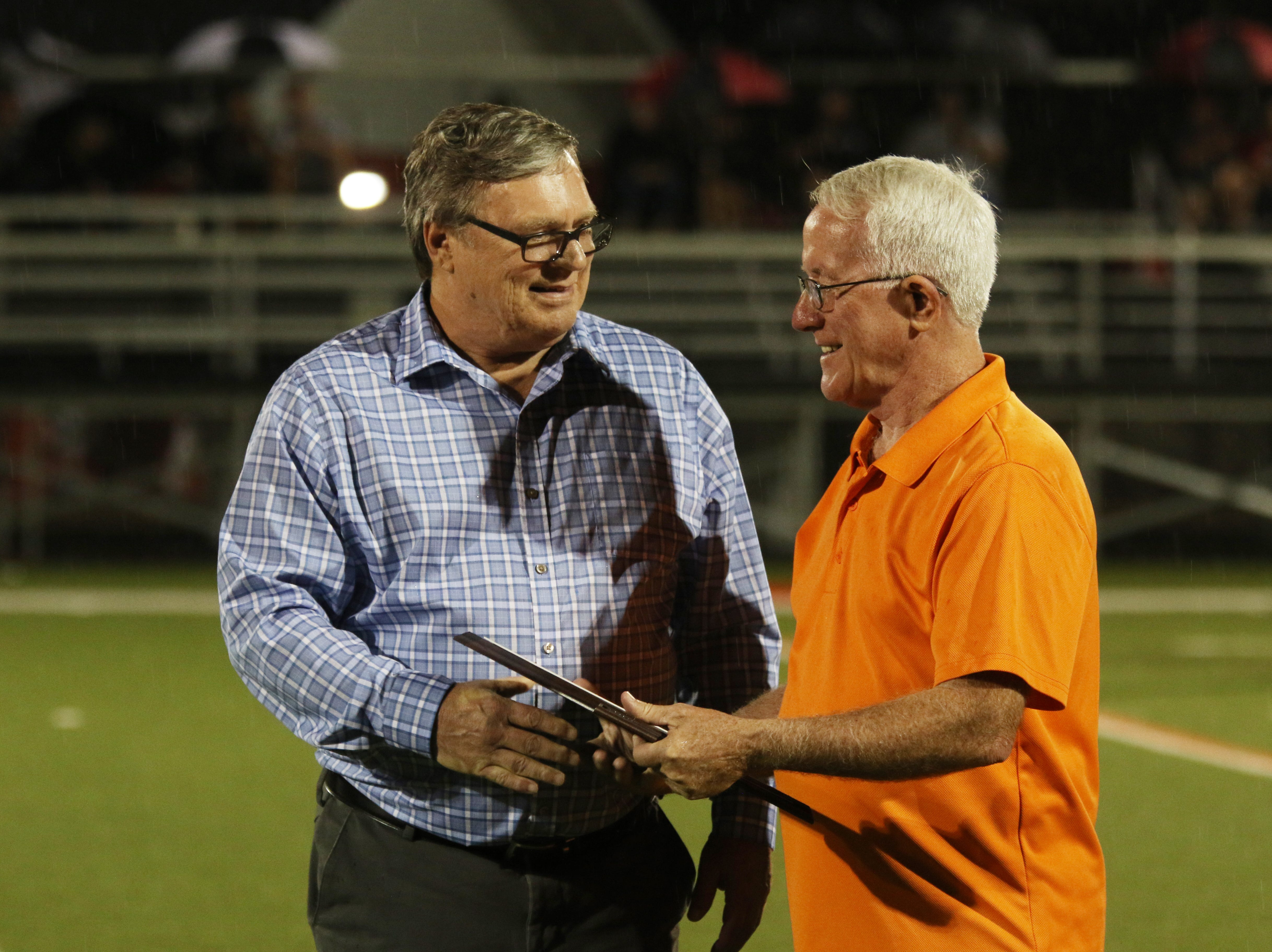 Mike Hill, left, is inducted into the New Lexington High School Hall of Fame on Friday.