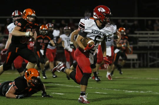Coshocton's Andew Kittell carries the ball against New Lexington.