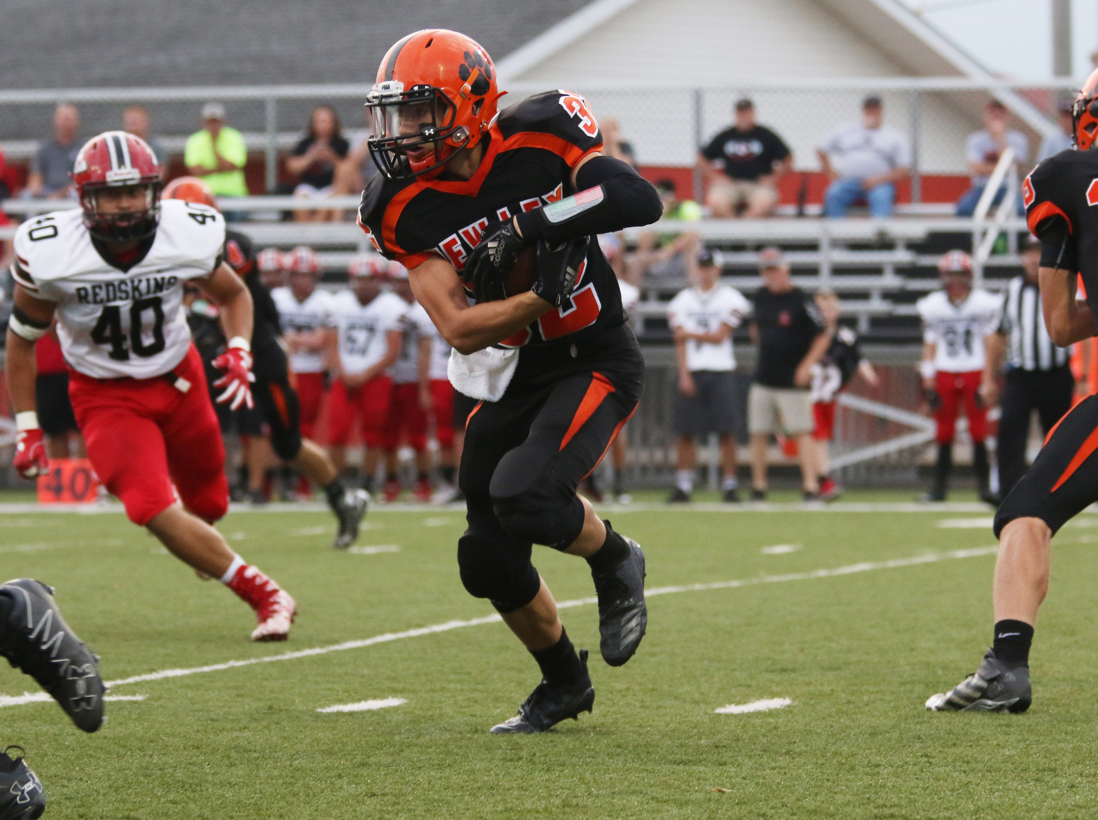 New Lexington's Blake Shepperd carries the ball against Coshocton.