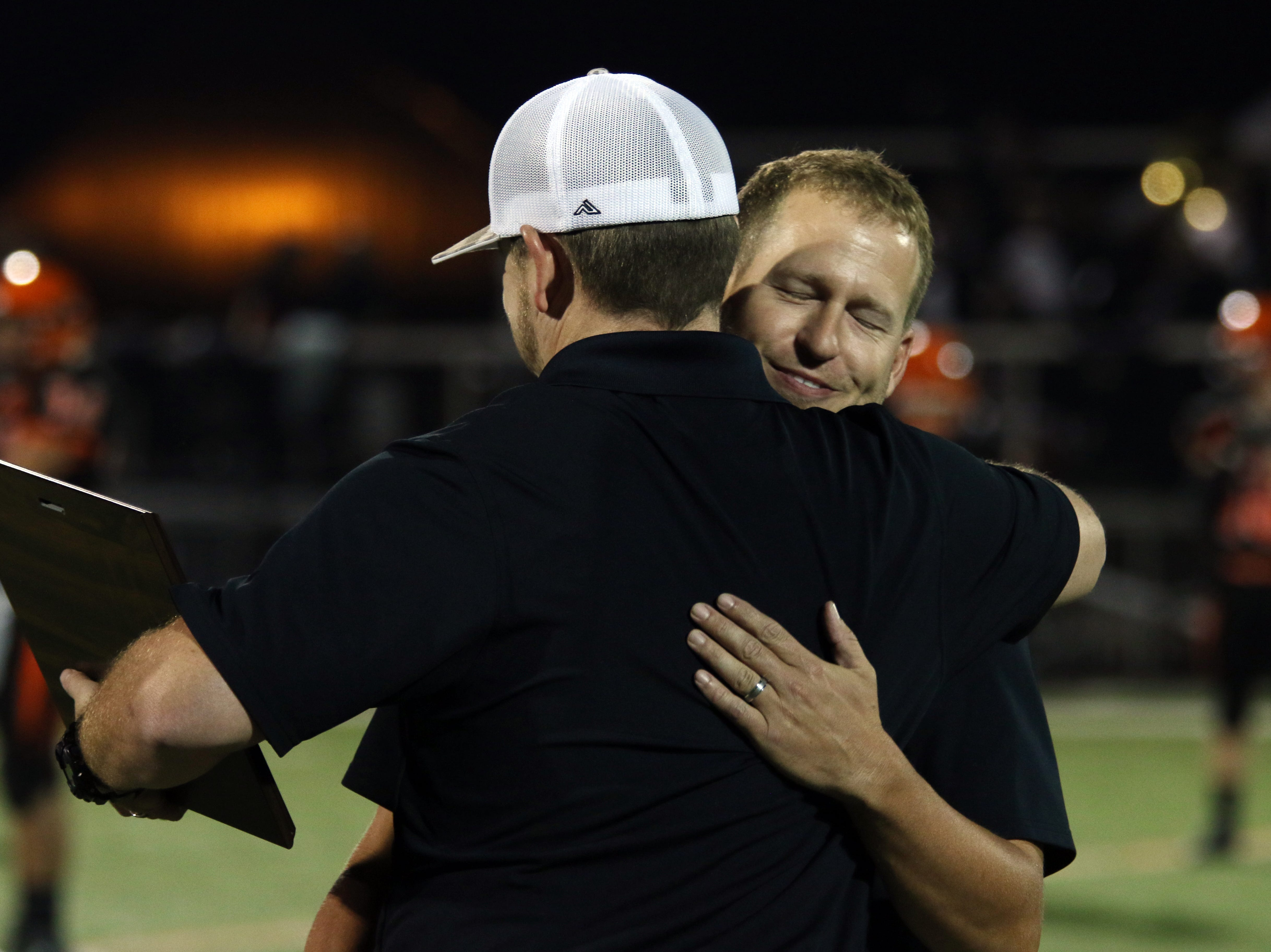 Kory Cook is gets a hug from Nate Wycinski after being inducted into the New Lexington High School Hall of Fame.