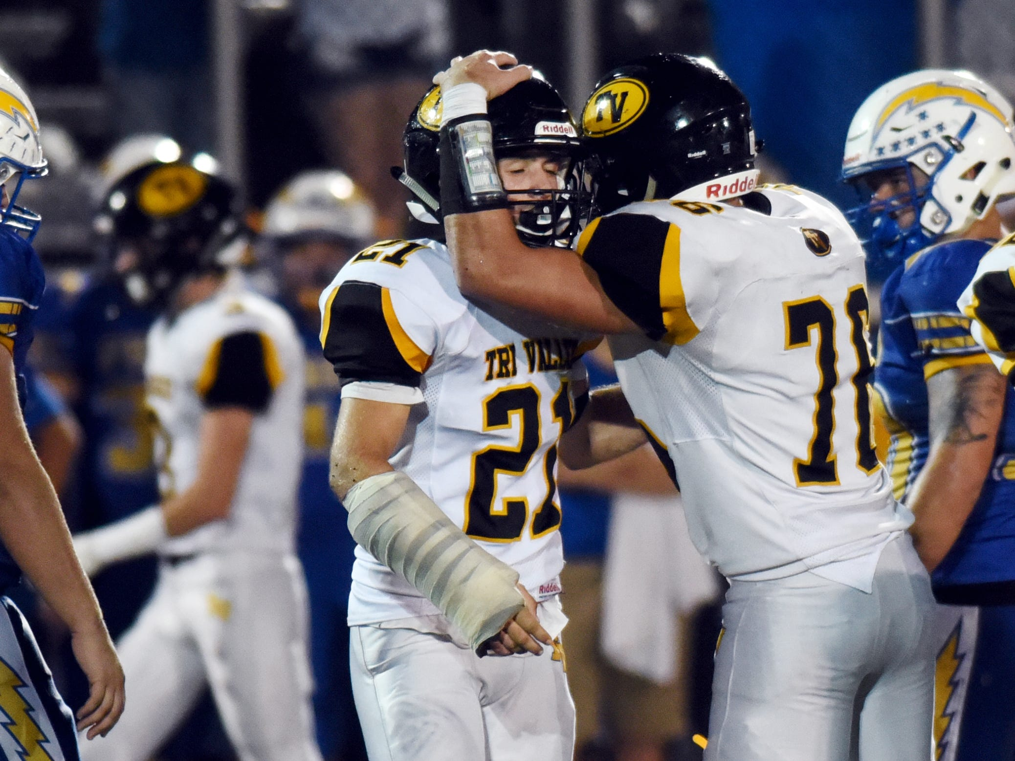 Tri-Valley's Blake Kendrick, left, is congratulated by Gyle Bradshaw after making a sack in the fourth quarter against Philo.