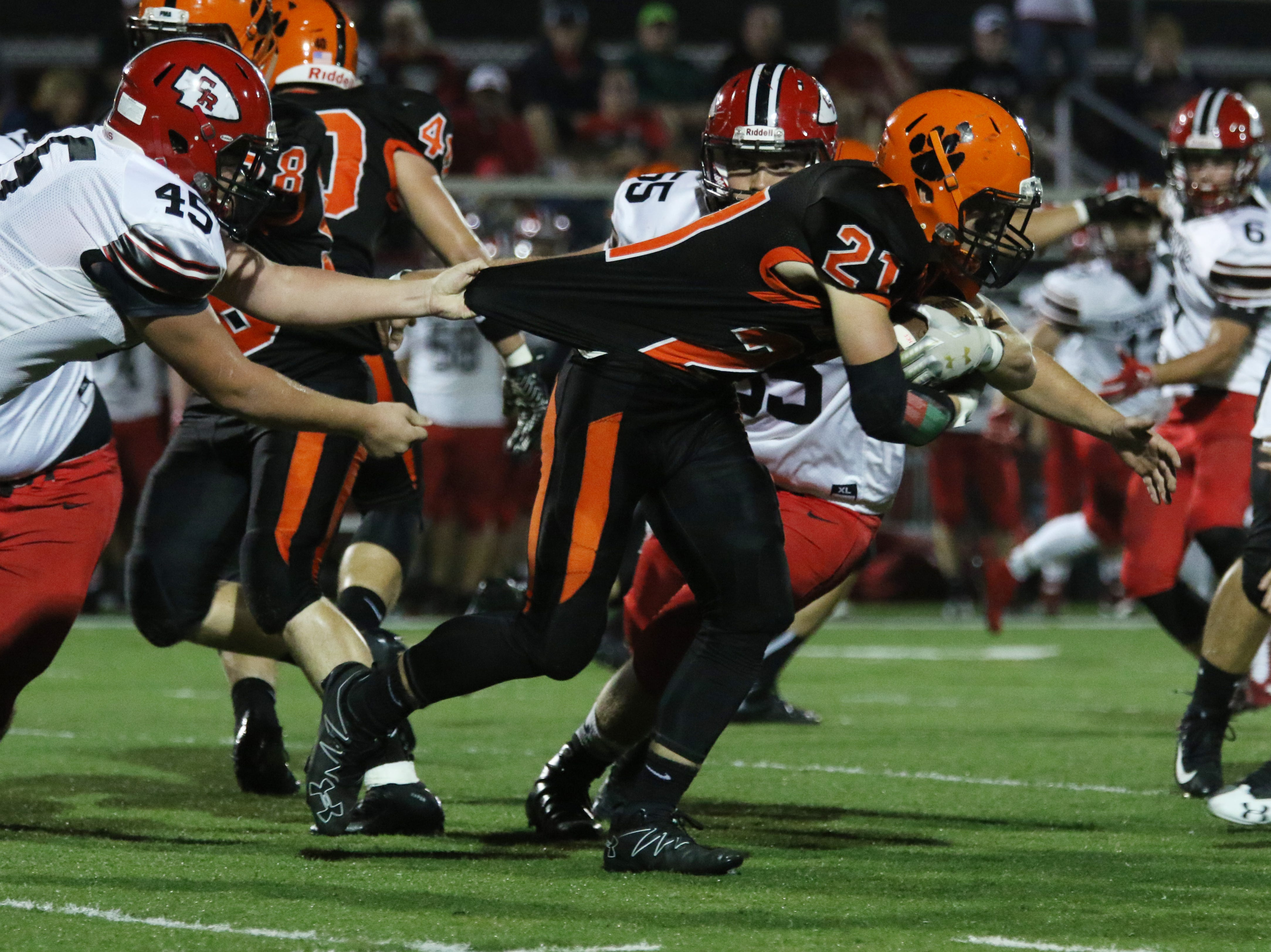 New Lexington's Christian Vance fights for yardage against Coshocton.