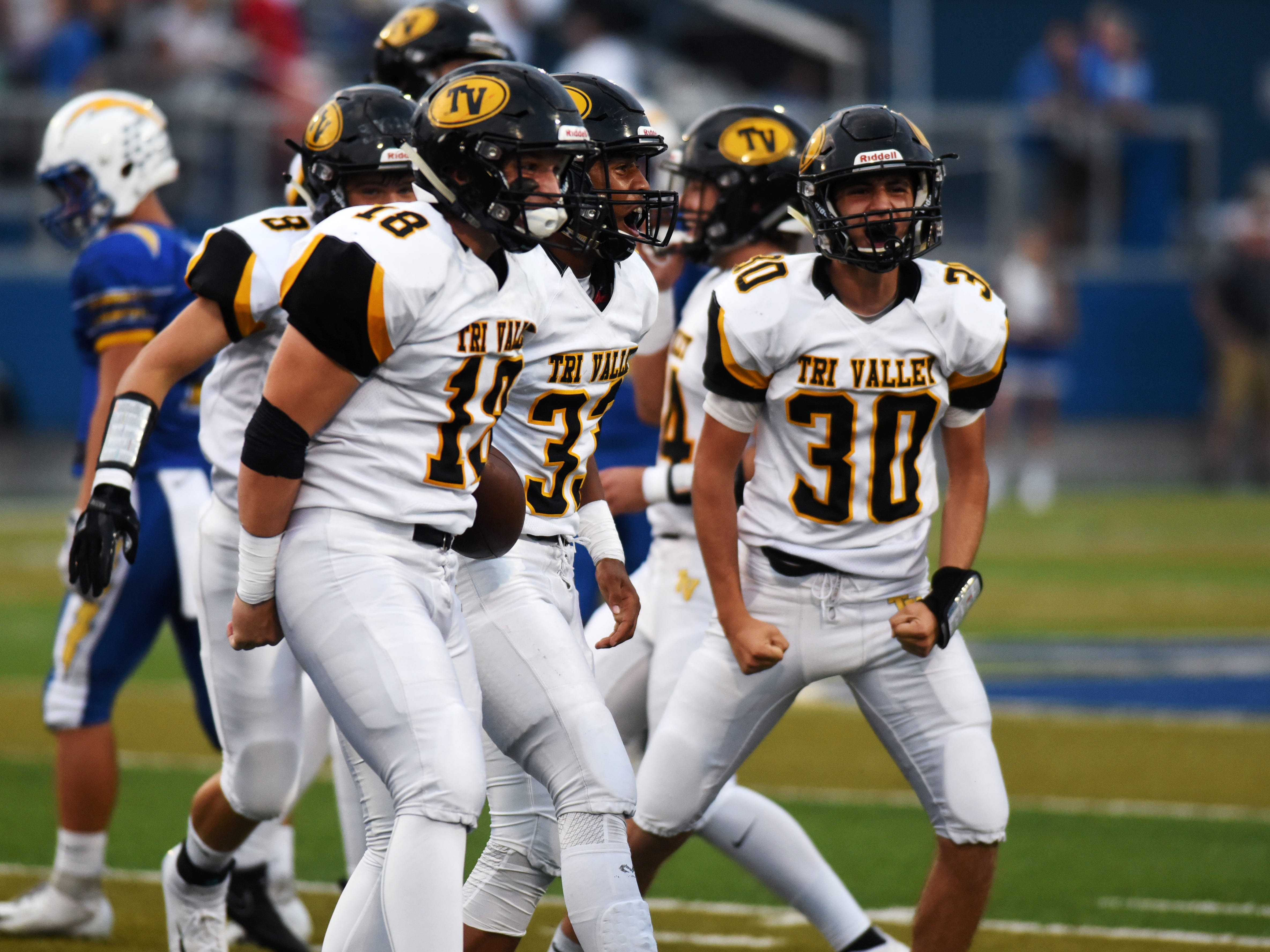 Tri-Valley players celebrate after Jordan Pantaleo, middle, recovered a fumble in the first half of a 28-14 comeback win against Philo on Friday night at Sam Hatfield Stadium.