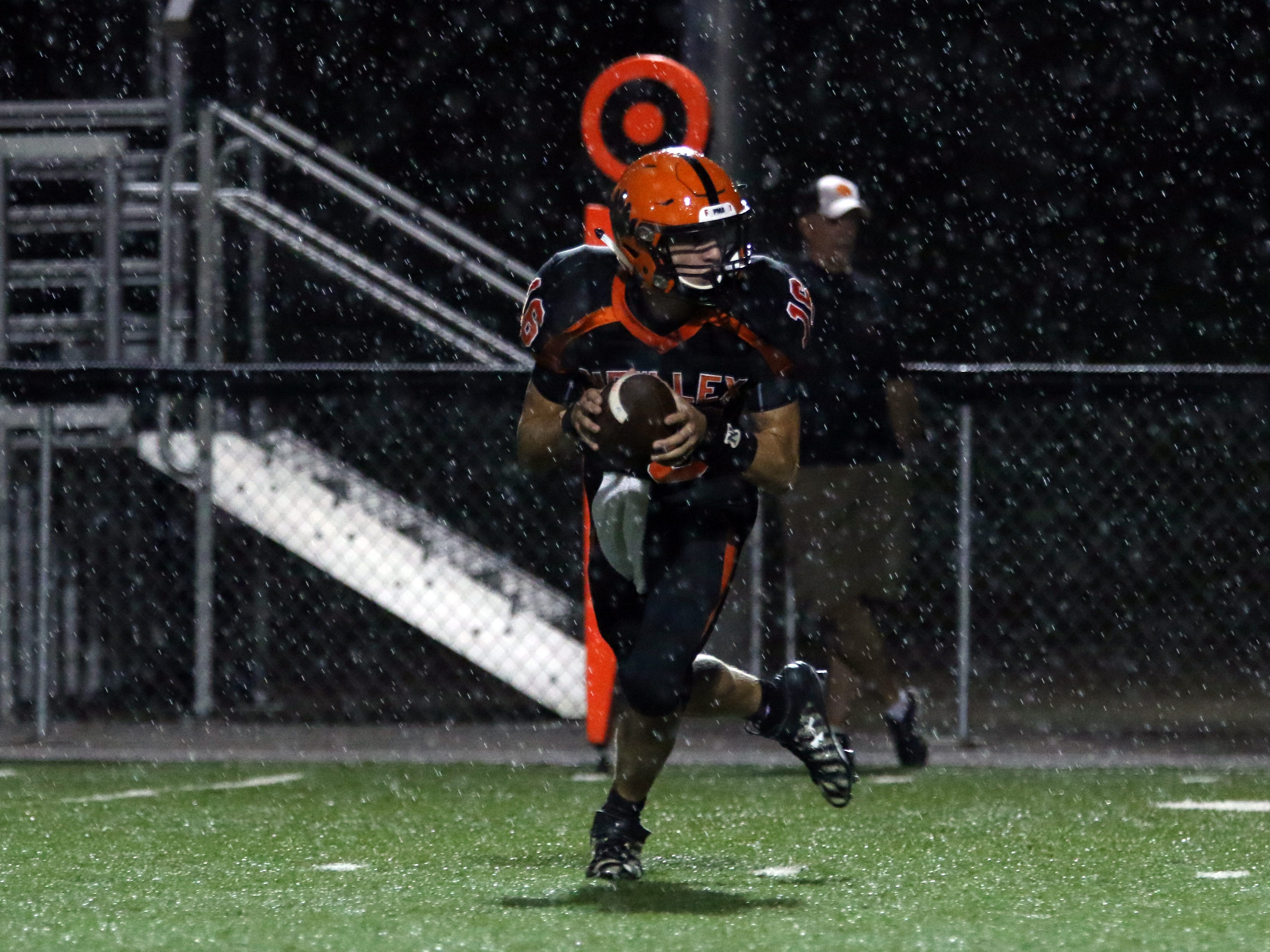 New Lexington's Logyn Ratliff rolls out of the pocket against Coshocton in the rain.