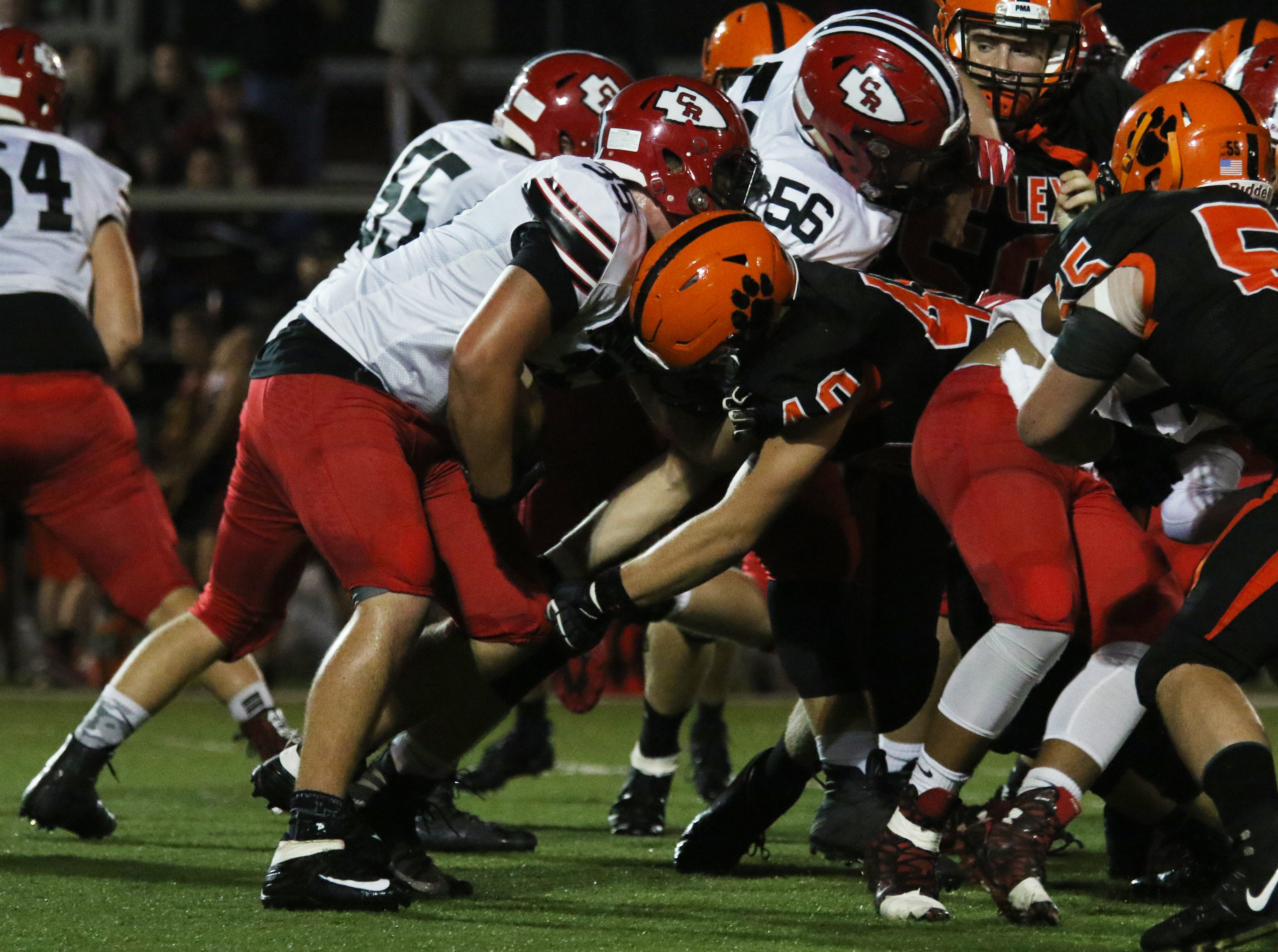 New Lexington's Seth Burgess stops Coshocton's Zach Bradford at the line of scrimmage.