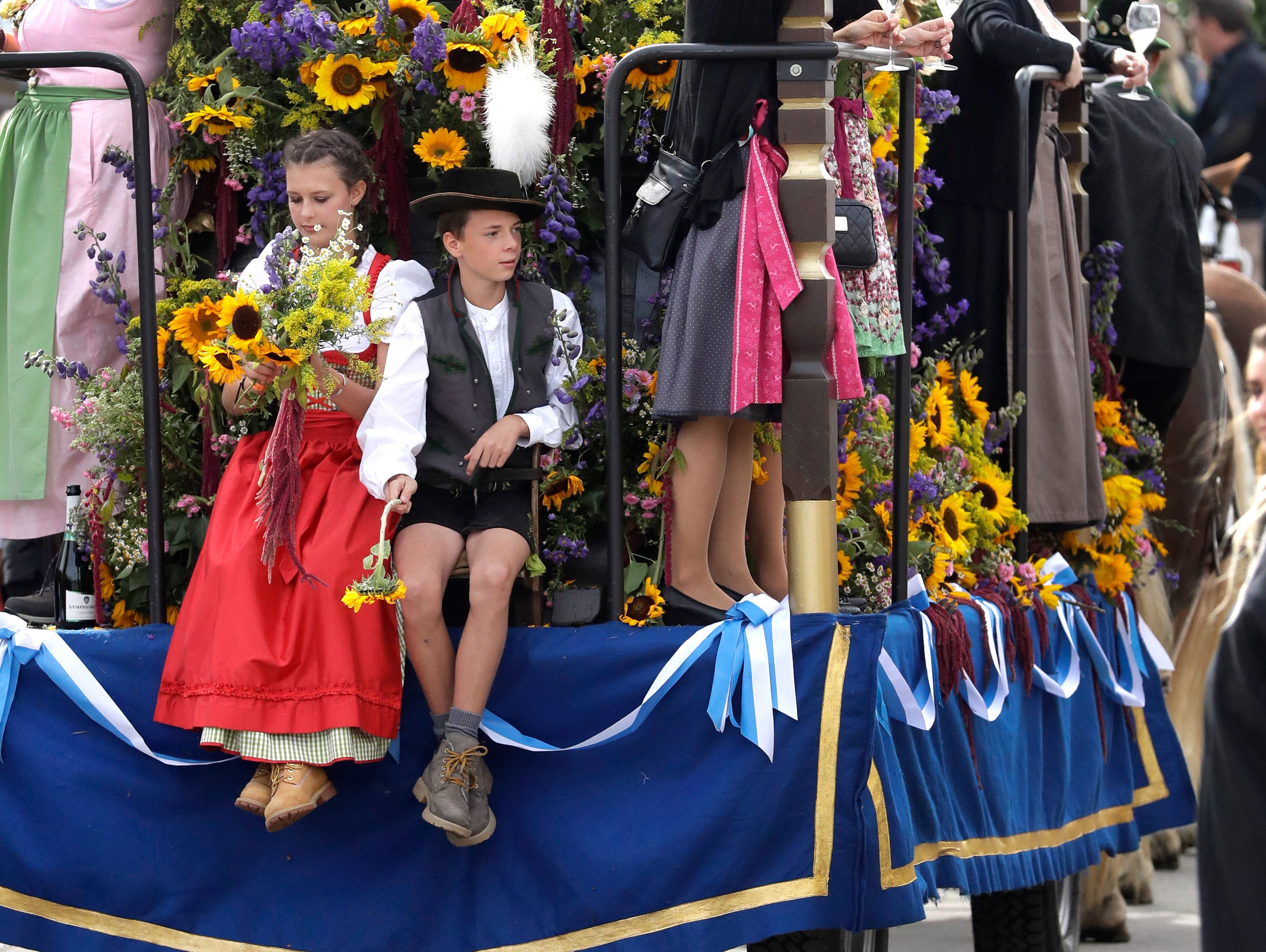 A girl and a boy sit on a wain during a parade as part of the opening of the Oktoberfest.