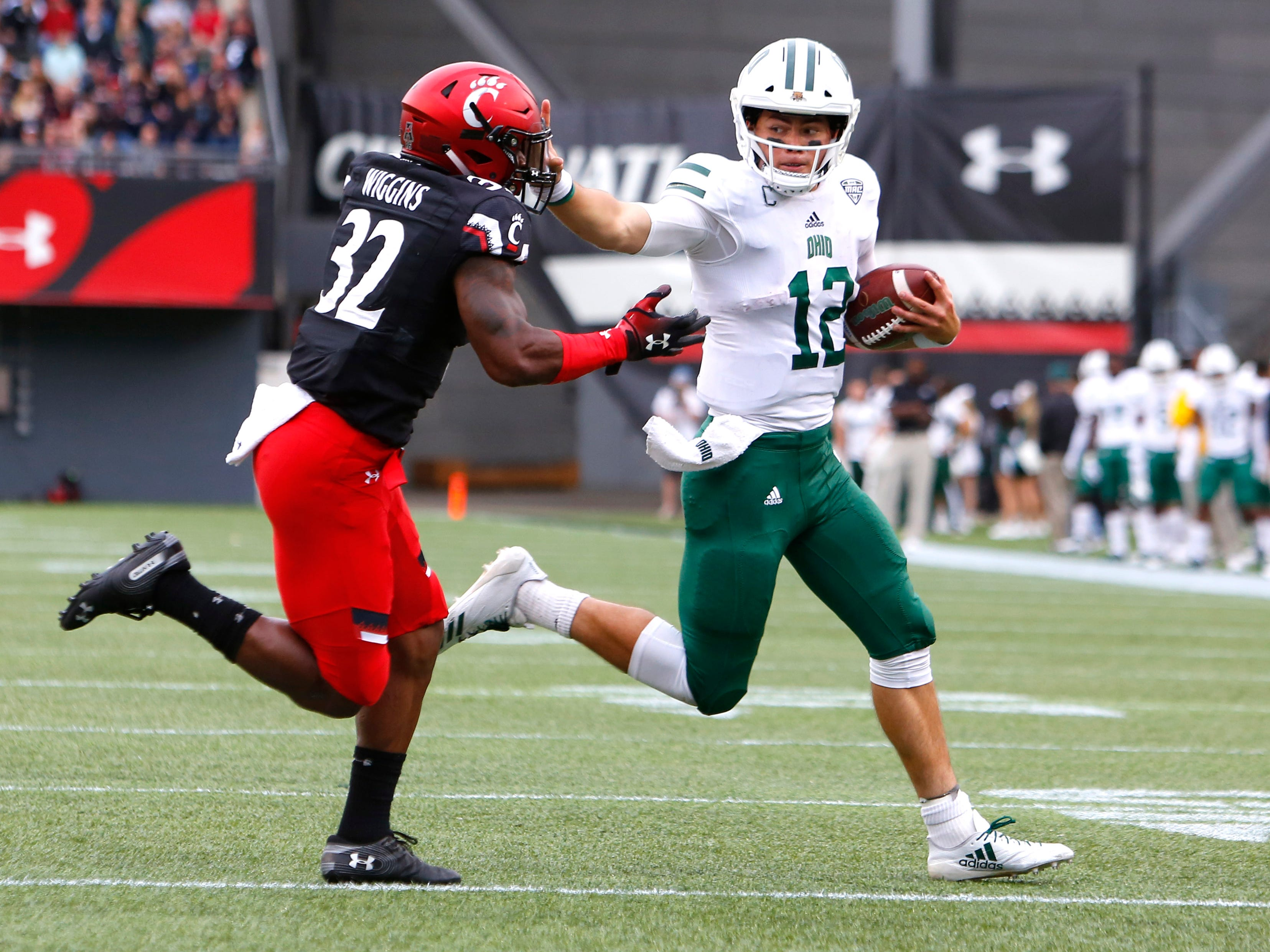 Sep 22, 2018; Cincinnati, OH, USA; Ohio Bobcats quarterback Nathan Rourke (12) runs against Cincinnati Bearcats safety James Wiggins (32) during the first half at Nippert Stadium. Mandatory Credit: David Kohl-USA TODAY Sports