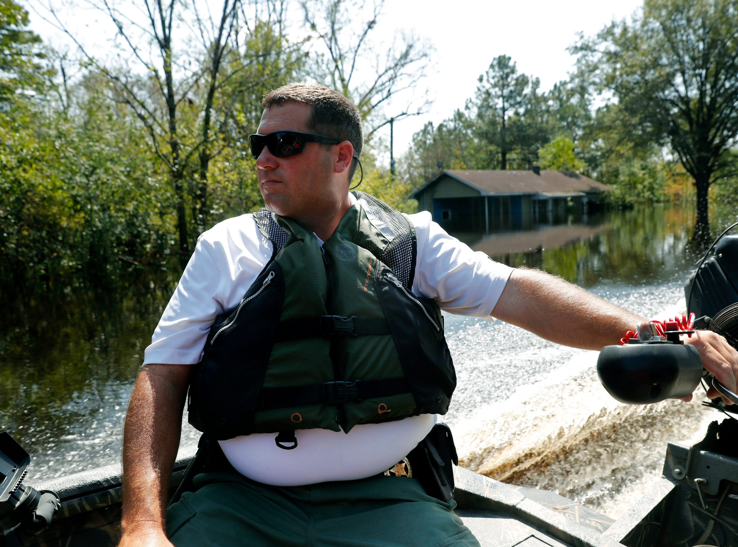Department of Natural Resources agent James Mills Cody patrols through floodwaters in the aftermath of Hurricane Florence in Nichols, S.C.