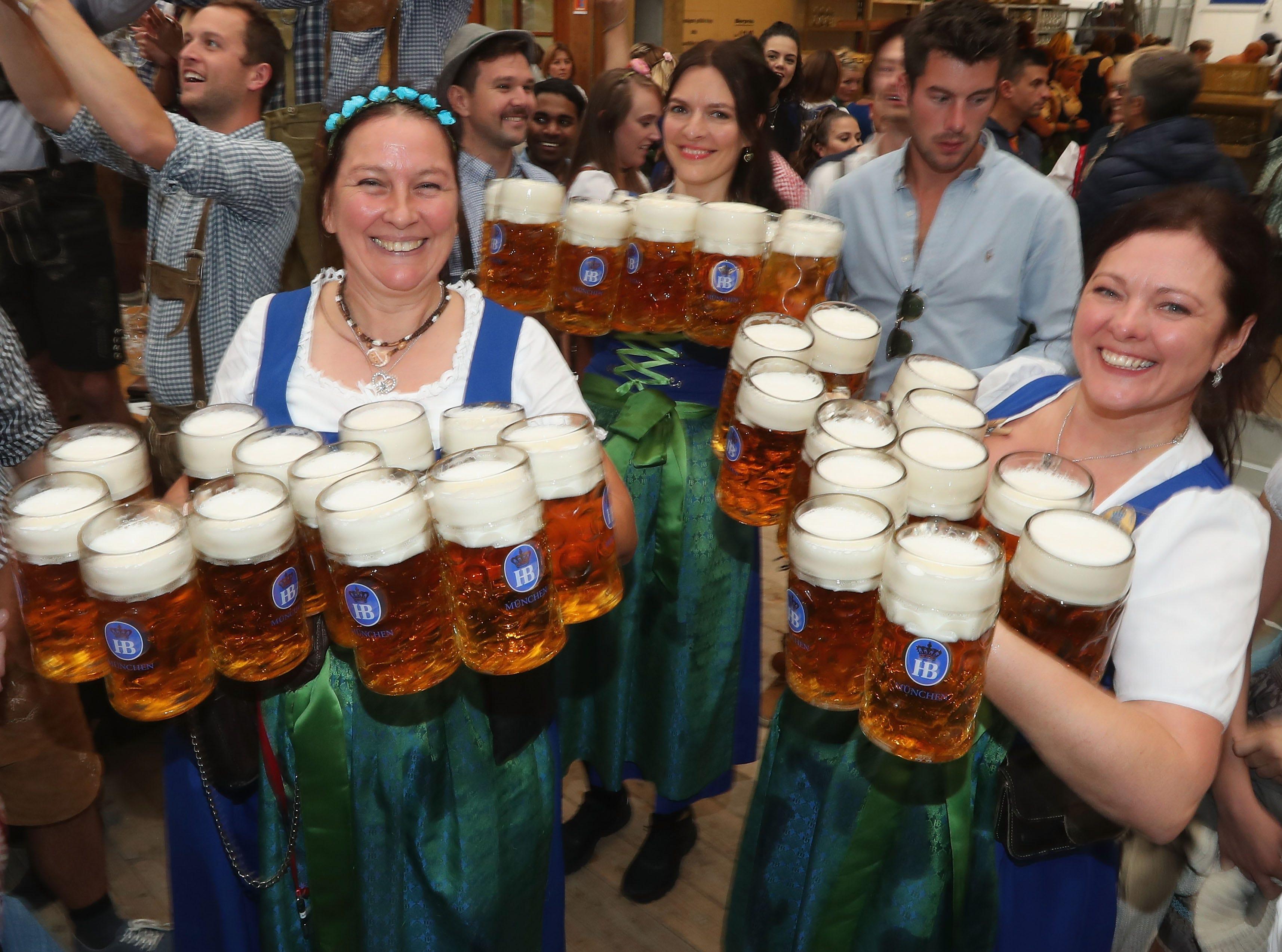 Waitresses carrying a dozen beer steins each.
