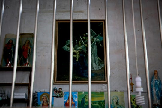 In this Tuesday, March 27, 2018, photo, Catholic religious paintings and figures are displayed behind bars at an underground Catholic church in Jiexi county in south China's Guangdong province. A group that monitors Christianity in China says the government is ratcheting up a crackdown on congregations in Beijing and several Chinese provinces, destroying crosses, burning Bibles and ordering followers to sign papers renouncing their faith.