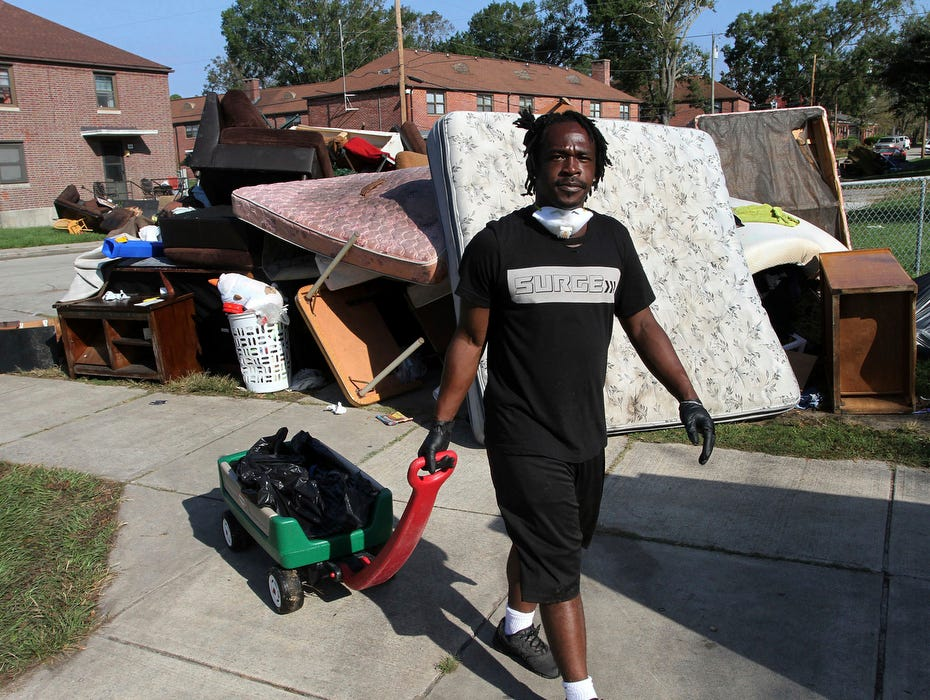 Volunteer Johnnie Evans brings a wagon of water, Friday, to cleanup crews helping with the grisly task of removing storm damaged belongings, spoiled food and soaked furniture at Trent Court Apartments in New Bern, N.C.