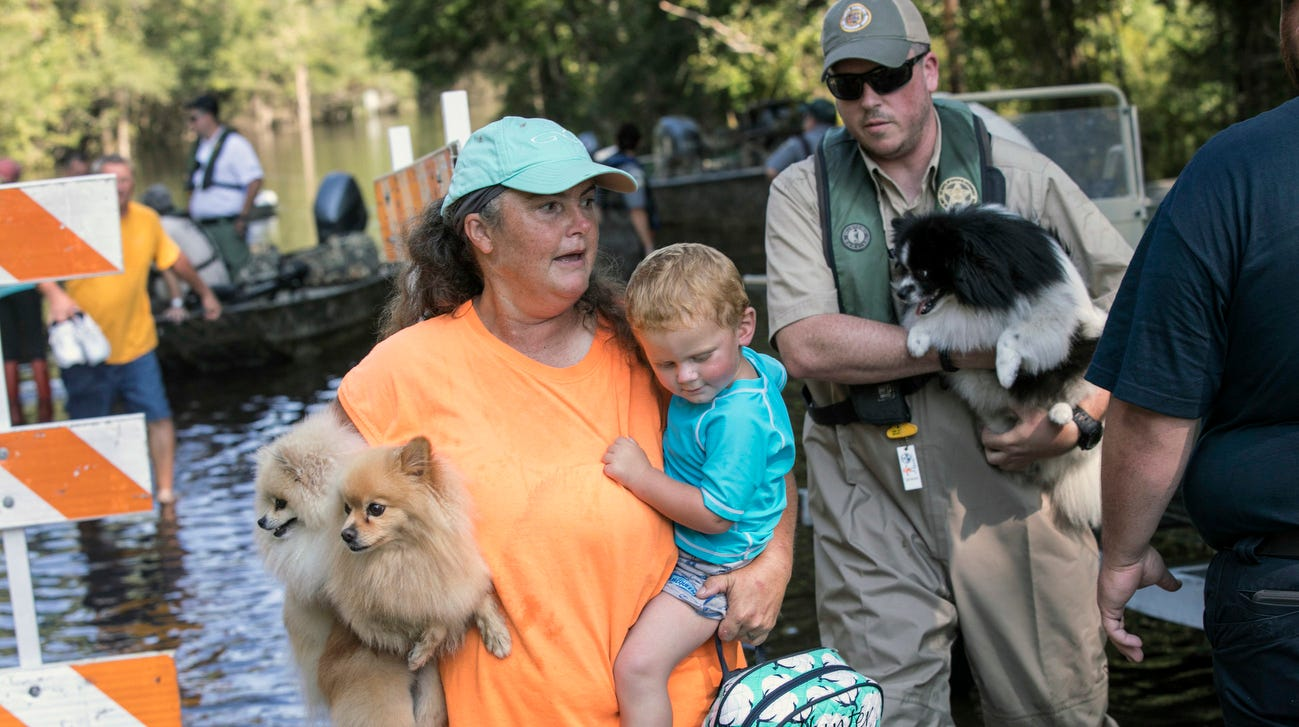 Denise Milligan holds her grandson, 2-year-old Hunter, and two of her dogs above the water as she is escorted to dry ground at Lee's Landing Circle, Sept. 21, 2018 in Conway, S.C.  With muddy river water still washing over entire communities on Friday, eight days after Hurricane Florence slammed into land with nearly 3 feet of rain, new evacuation orders forced residents to flee to higher ground amid a sprawling disaster that's beginning to feel like it will never end.