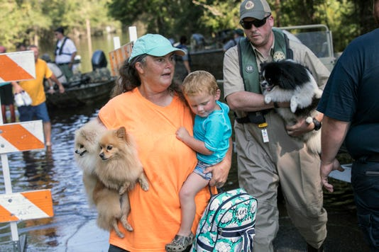 Denise Milligan holds her grandson, 2-year-old Hunter, and two of her dogs above the water as she is escorted to dry ground at Lee's Landing Circle, Sept. 21, 2018 in Conway, S.C. With muddy river water still washing over entire communities on Friday, eight days after Hurricane Florence slammed into land with nearly 3 feet of rain, new evacuation orders forced residents to flee to higher ground amid a sprawling disaster that's beginning to feel like it will never end. (Photo: Jason Lee/AP)