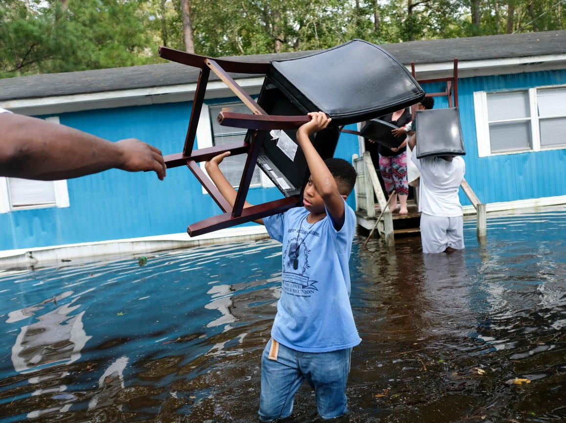 T.J. Williams, age 12, helps remove chairs from his family home on Collins street where his family were removing their belongings ahead of rising waters, Friday, in Longs, S.C.