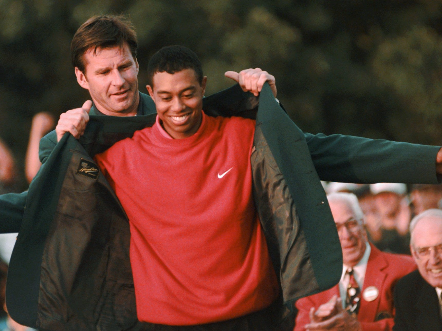 On April 13, 1997, Tiger Woods receives his first green jacket as Masters champion from Nick Faldo at Augusta National Golf Club.