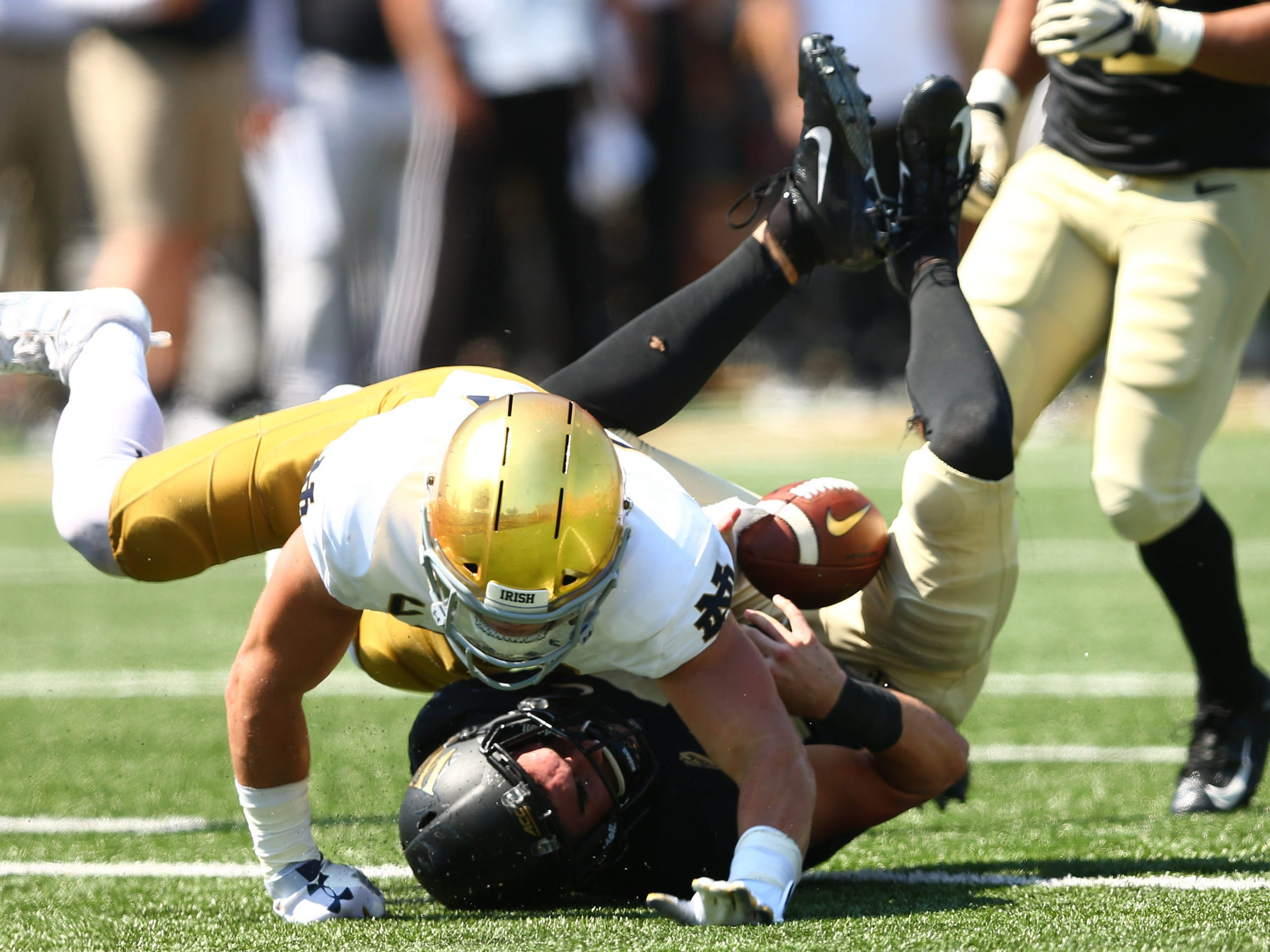 Wake Forest quarterback Sam Hartman gets sacked by Notre Dame linebacker Drue Tranquill in the second quarter at BB&T Field.