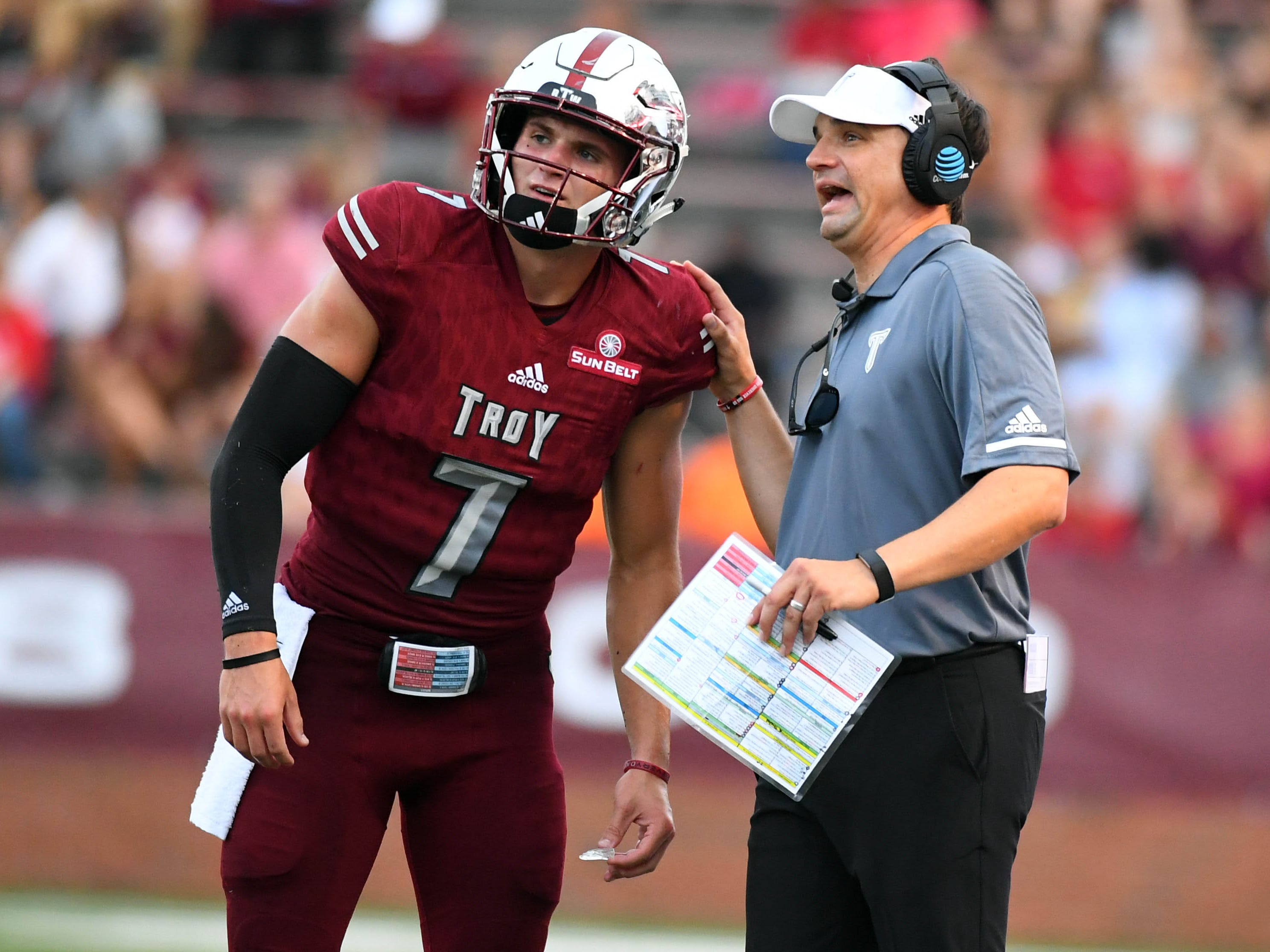 Troy Trojans head coach Neal Brown talks with quarterback Kaleb Barker (7) during the first half against the Boise State Broncos at Veterans Memorial Stadium.