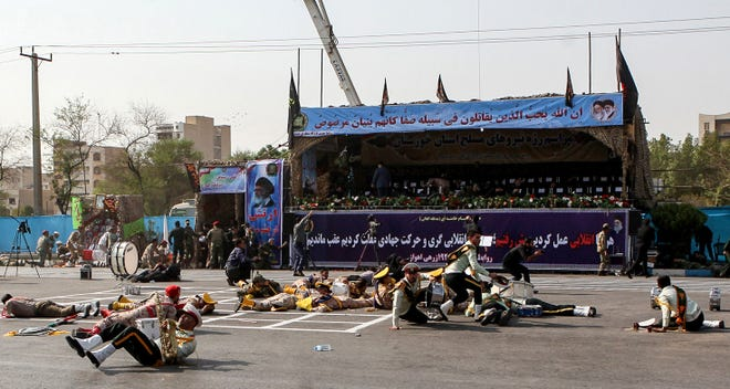 This picture taken on September 22, 2018 in the southwestern Iranian city of Ahvaz shows injured soldiers lying on the ground at the scene of an attack on a military parade that was marking the anniversary of the outbreak of its devastating 1980-1988 war with Saddam Hussein's Iraq.