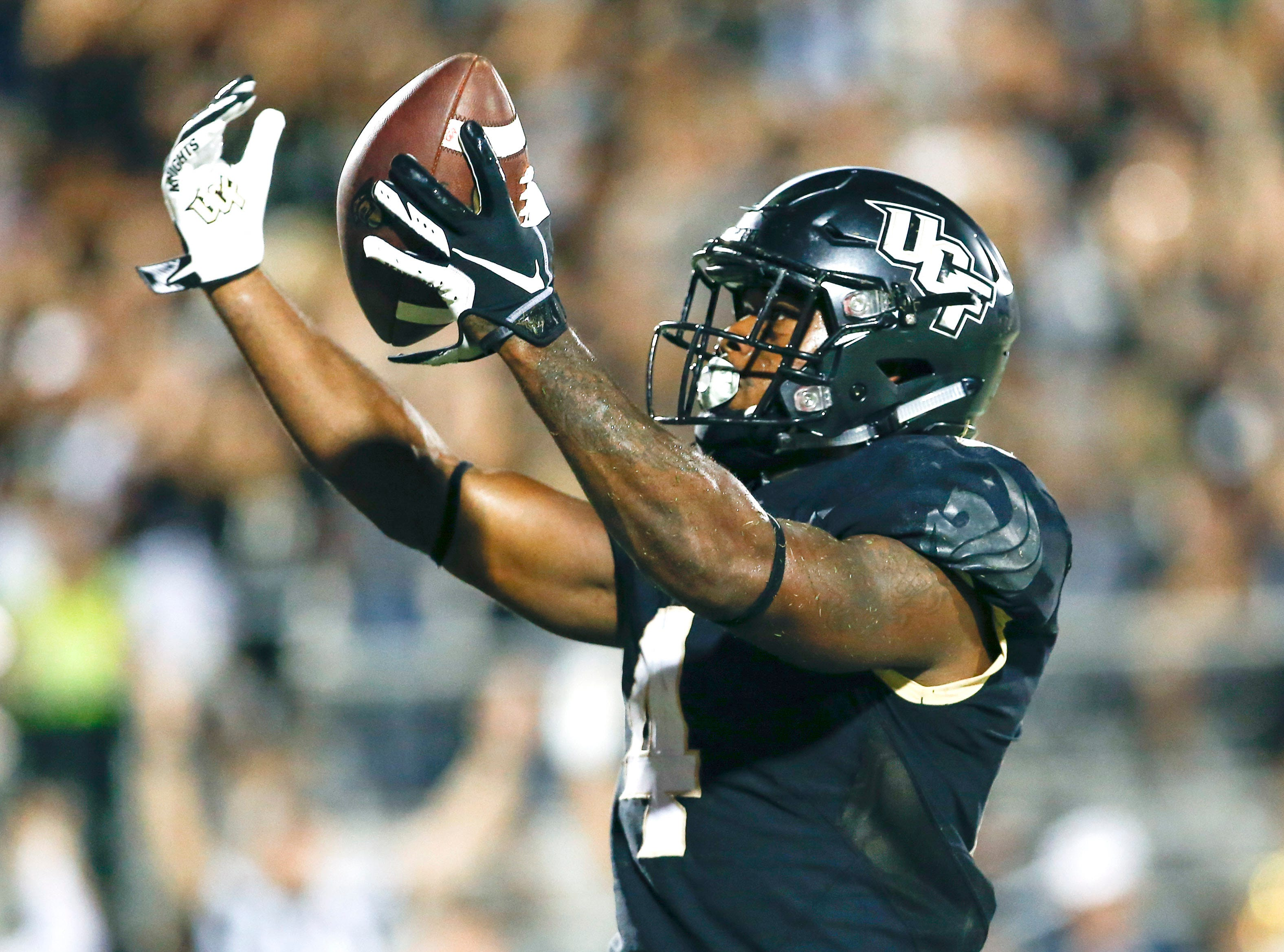 UCF Knights running back Taj McGowan (4) reacts after his rushing touchdown during the second half against the Florida Atlantic Owls at Spectrum Stadium.