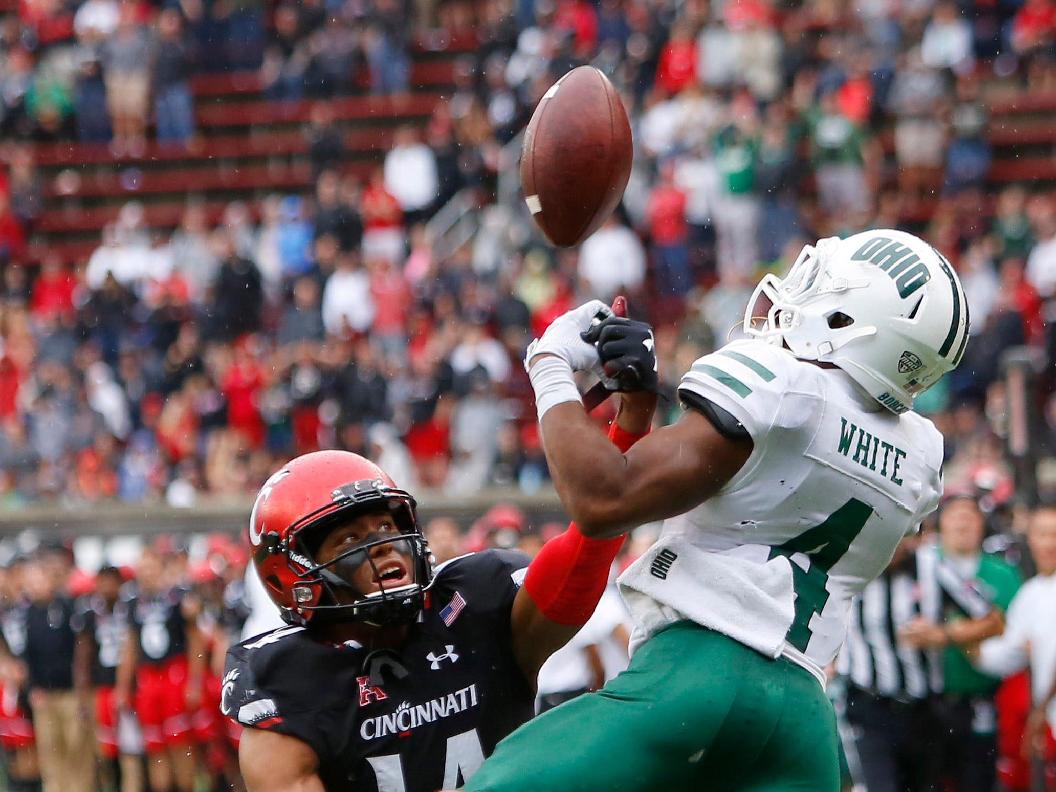 Cincinnati Bearcats cornerback Cameron Jefferies (14) breaks up a pass against Ohio Bobcats cornerback Jamal Hudson (4) during the second half at Nippert Stadium.