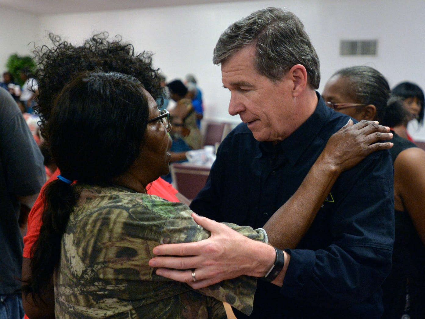 North Carolina Governor Roy Cooper talks with Joyce Davis at an event feeding victims of Hurricane Florence at the Bright Hopewell Baptist Church, Friday,  in Laurinburg, N.C.. Gov. Roy Cooper said the damage in his state is in the billions of dollars, but there was no way to make a more accurate estimate while flooding continues.