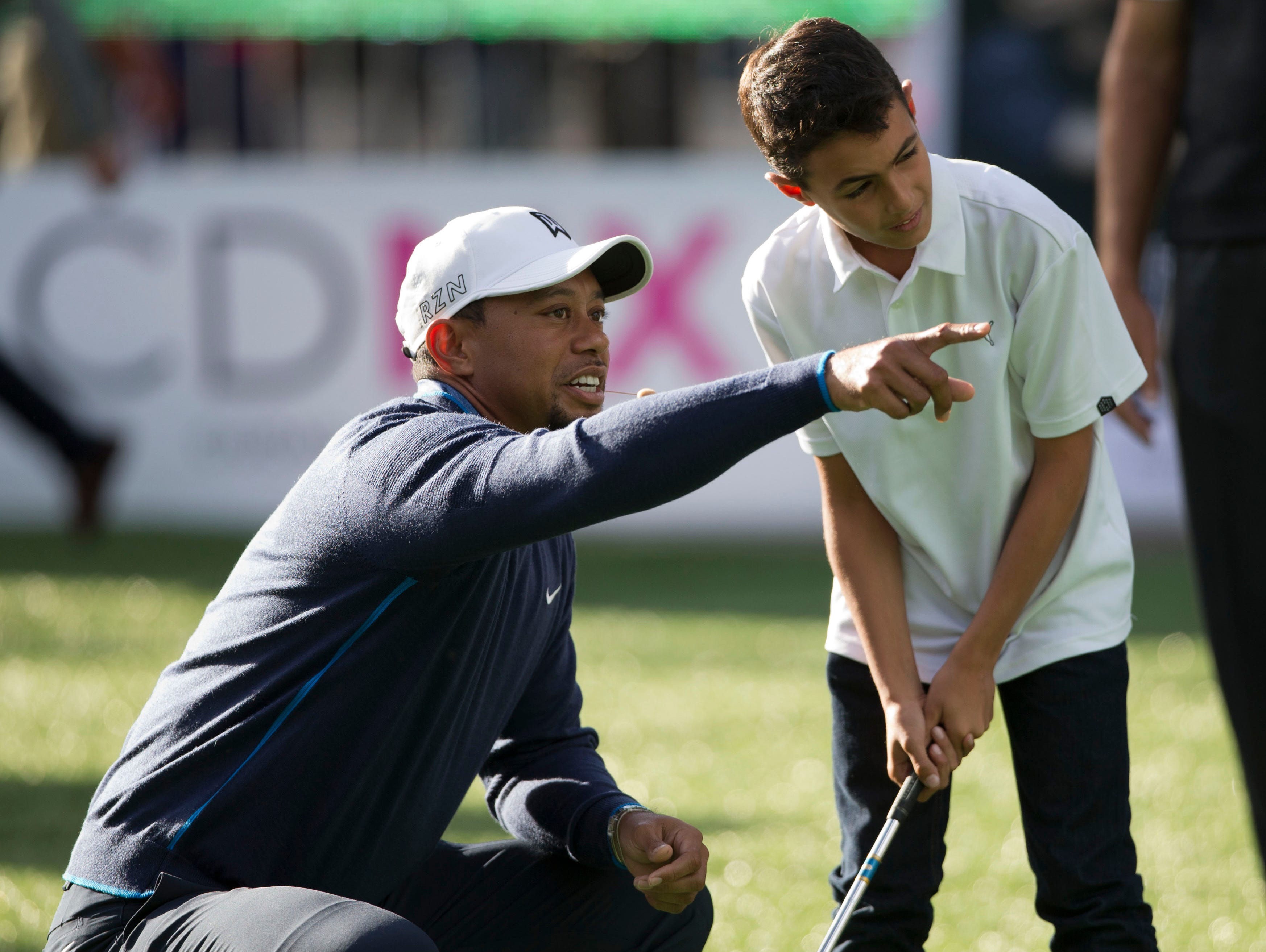 Woods has another back surgery in October 2015. Shown here Woods gives pointers to  a young golfer, during a promotional clinic as part of the Bridgestone America's Golf Cup in Mexico City on  Oct. 20, 2015.