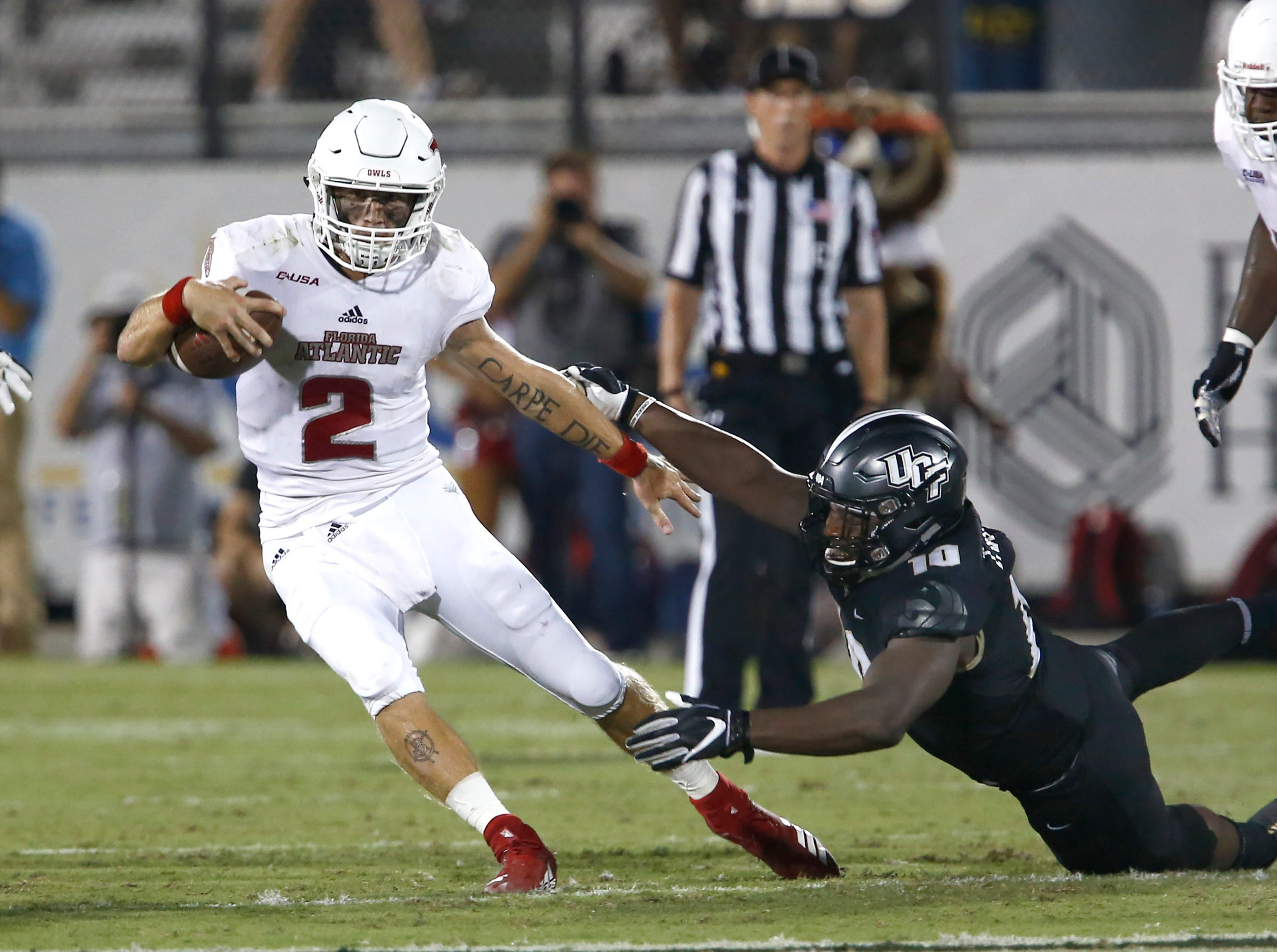 Florida Atlantic Owls quarterback Chris Robison (2) slips out of the grasp of UCF Knights defensive lineman Titus Davis (10) during the second quarter at Spectrum Stadium.