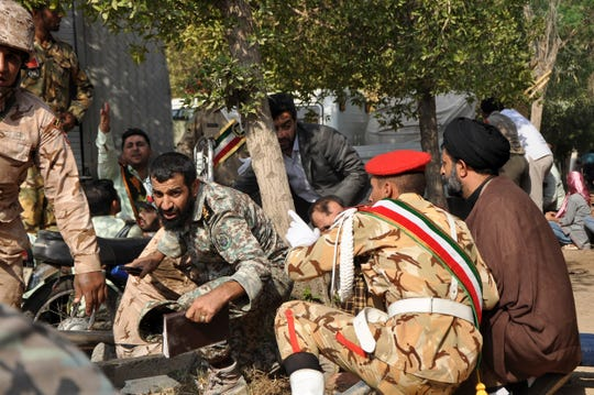 In this photo provided by the Iranian Students' News Agency, ISNA, Iranian armed forces members and civilians take shelter in a shooting during a military parade marking the 38th anniversary of Iraq's 1980 invasion of Iran, in the southwestern city of Ahvaz, Iran, Saturday, Sept. 22, 2018.