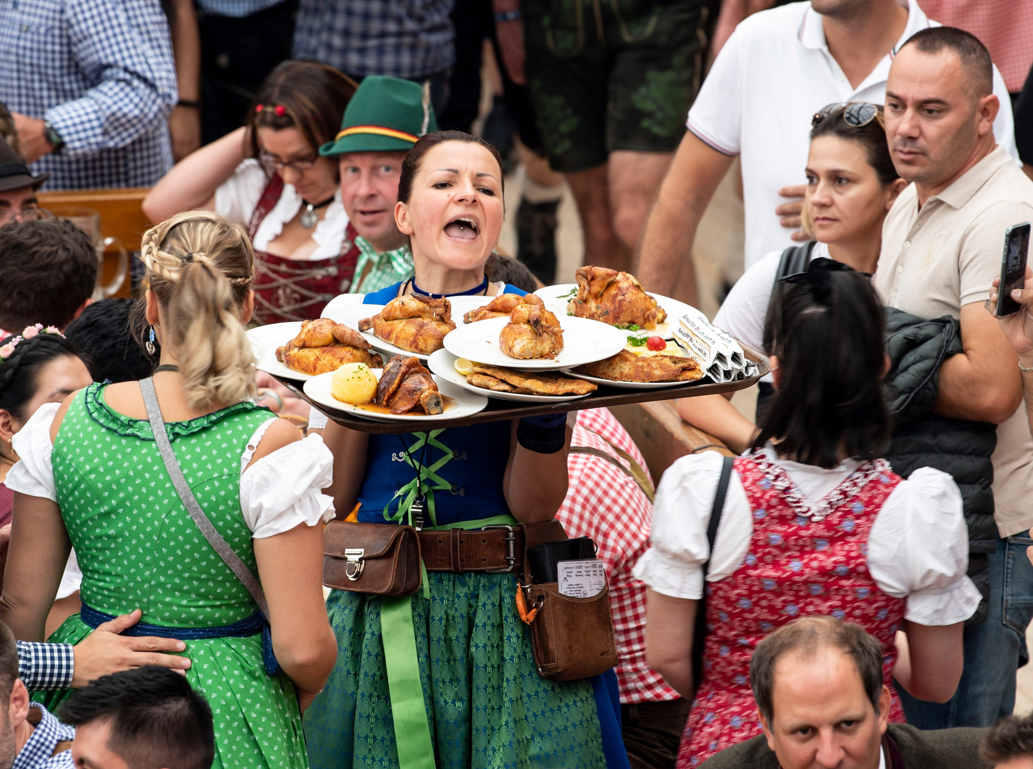 A waitress carries roasted chickens inside the Hofbraeu tent during opening day.
