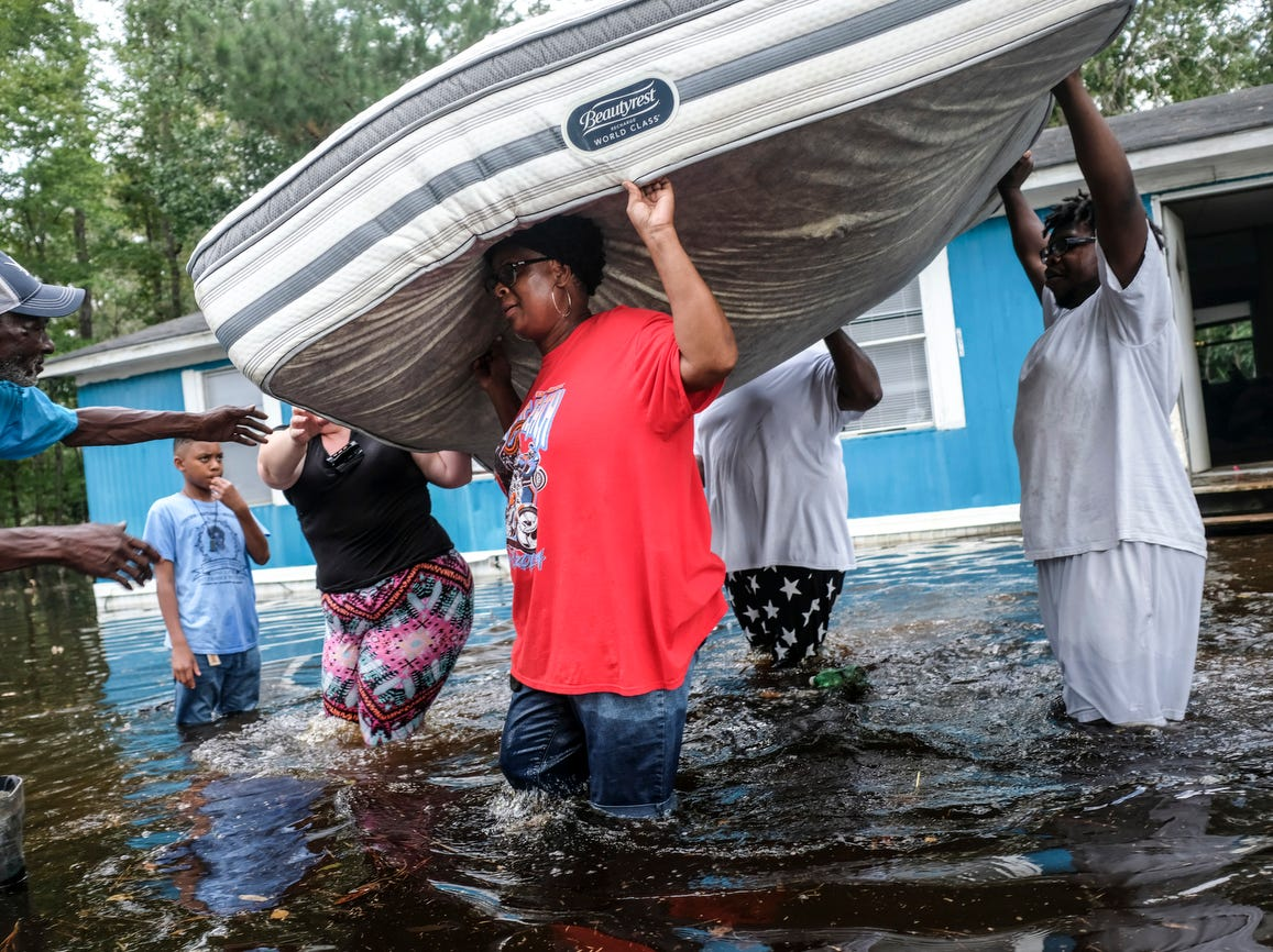 The Williams family rapidly removes their belongings trying to keep their mattresses dry, on Sept. 21, 2018 in Longs, S.C.. With muddy river water still washing over entire communities on Friday, eight days after Hurricane Florence slammed into land with nearly 3 feet of rain, new evacuation orders forced residents to flee to higher ground amid a sprawling disaster that's beginning to feel like it will never end.
