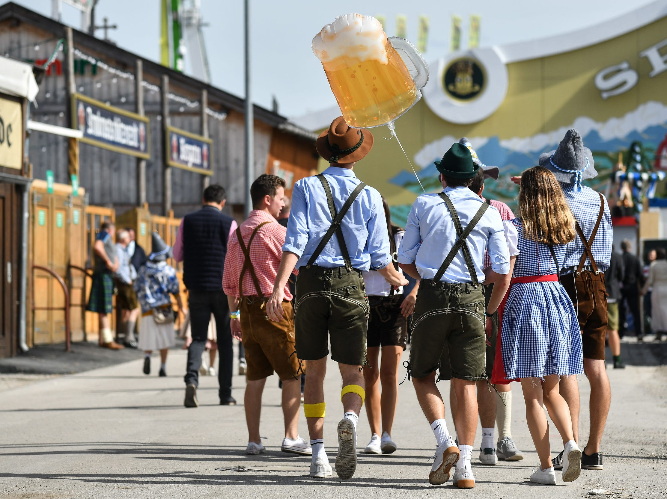 Revellers wearing traditional Alpine folk attire carry a balloon in the shape of a beer mug during the opening day.