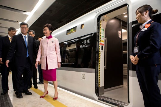 Ma Xingrui, governor of Guangdong Province, front row left, and Carrie Lam, Hong Kong's chief executive, front row second left, stand next to a Guangzhou-Shenzhen-Hong Kong Express Rail Link (XRL) Vibrant Express train bound for Guangzhou Nan Station waits in the Mainland Port Area at West Kowloon Station, which houses the terminal for the XRL in Hong Kong on Sept. 22, 2018.