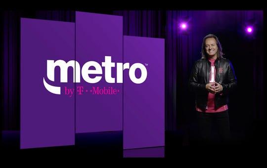 John Legere, CEO de T-Mobile, posa junto al nuevo logotipo de Metro by T-Mobile. MetroPCS se deshace de PCS en un cambio de nombre.