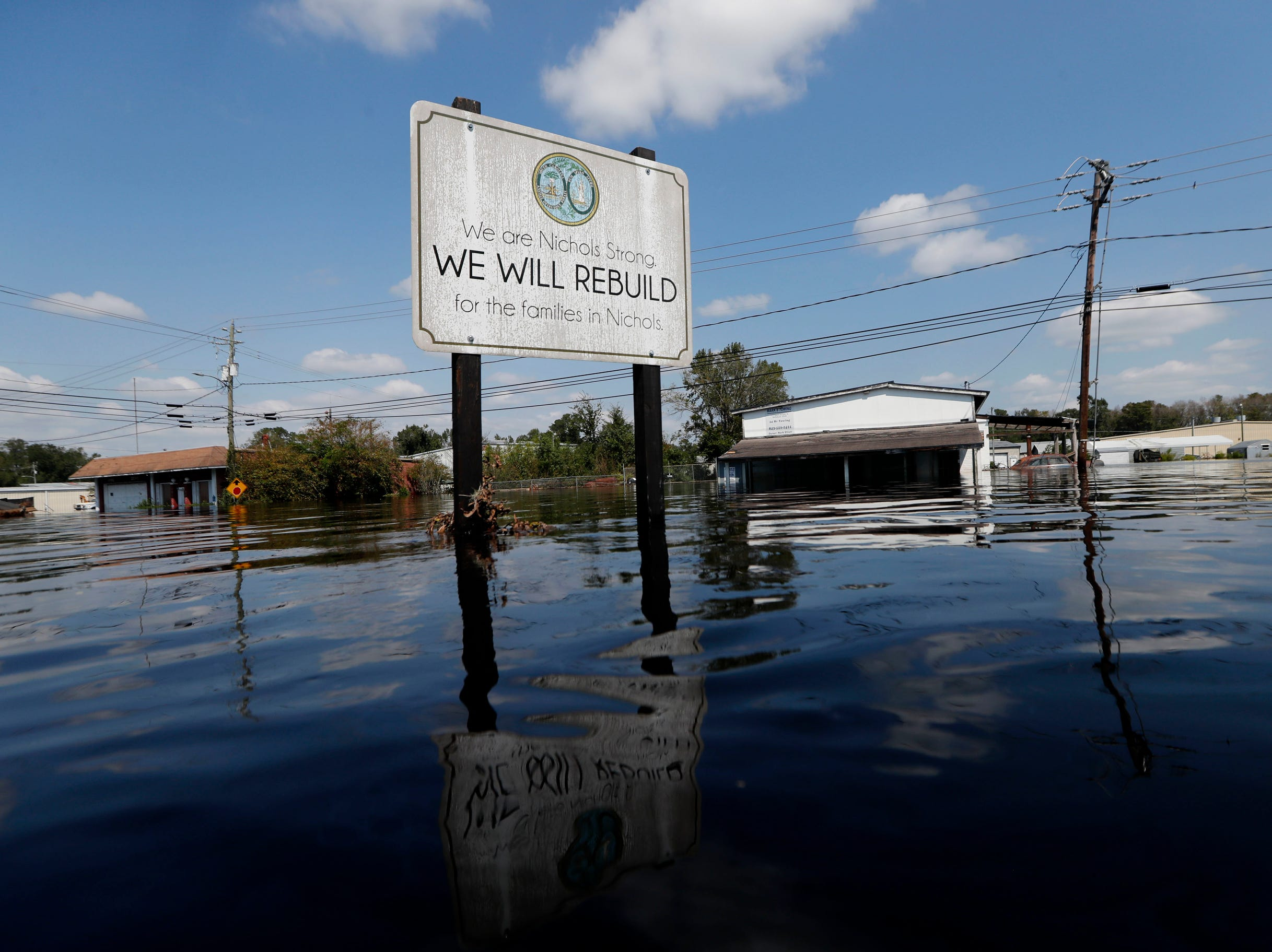 A sign commemorating the rebuilding of the town of Nichols, which was flooded two years earlier from Hurricane Matthew, stands in floodwaters in the aftermath of Hurricane Florence in Nichols, S.C., Friday. Virtually the entire town is once again flooded and inaccessible except by boat.