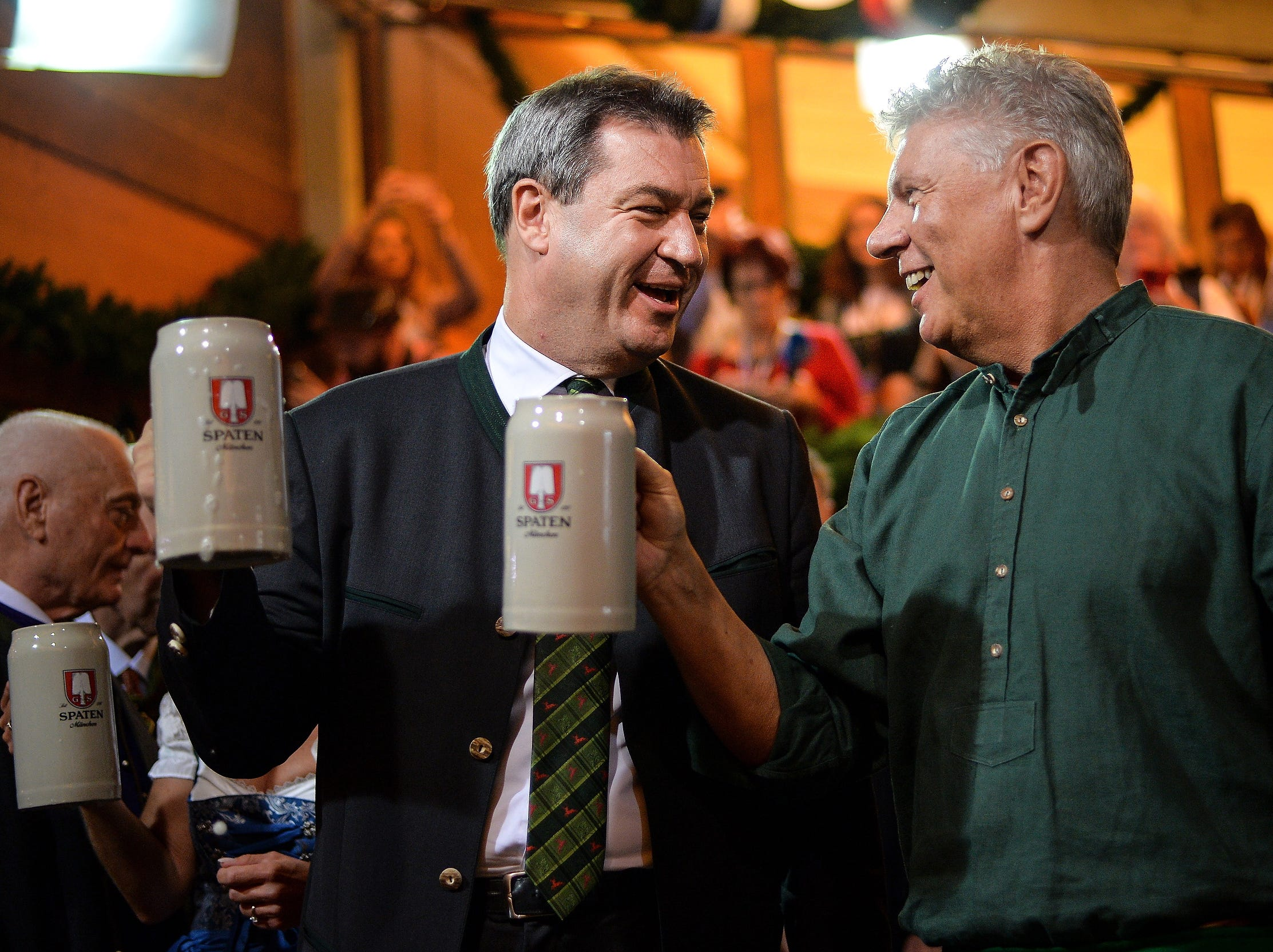 Bavarian prime minister Markus Soeder and Munich's lord mayor Dieter Reiter toast with the event's first beer steins during the festival's opening day.
