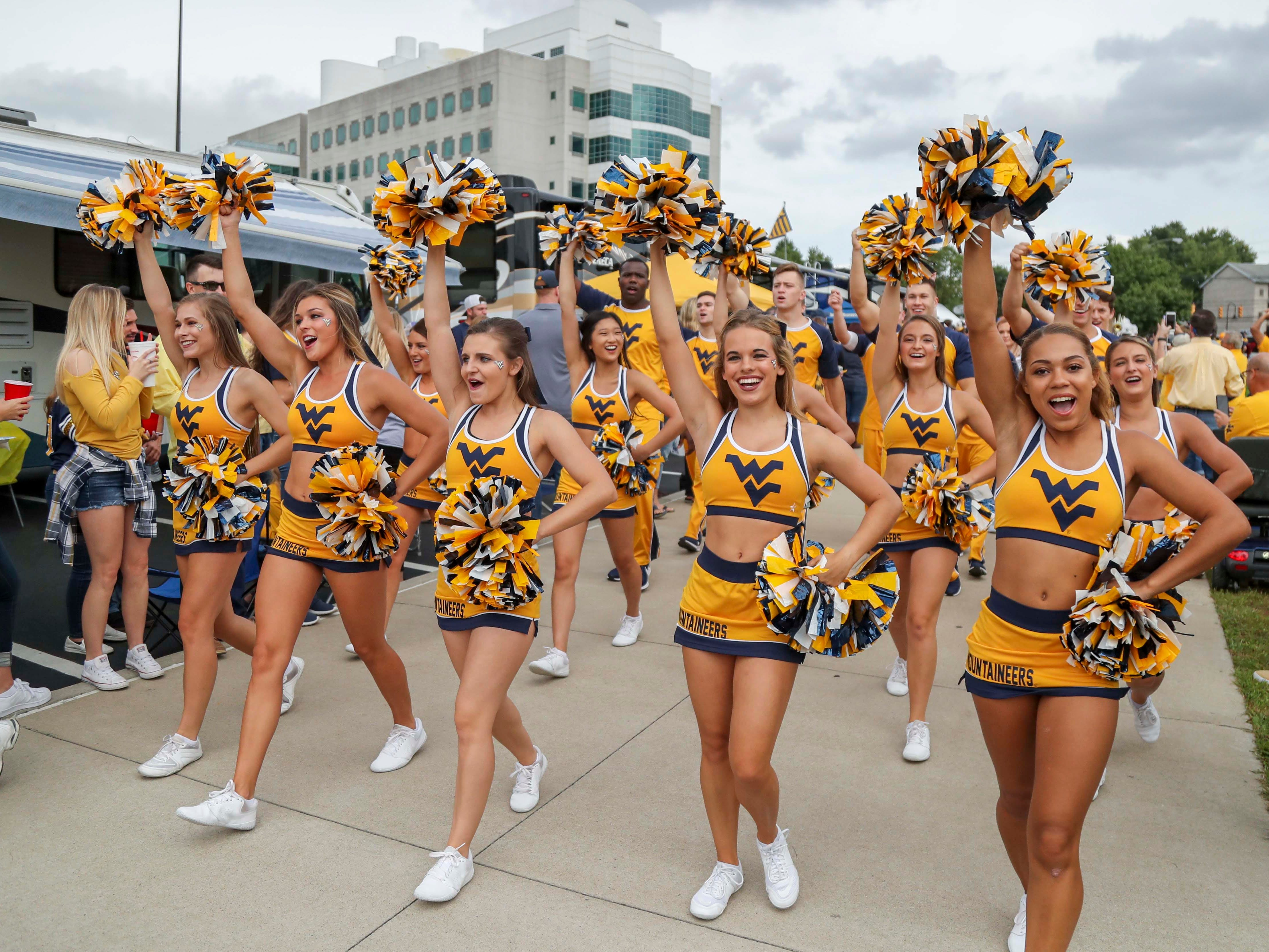 West Virginia Mountaineers cheerleaders lead the team into the stadium before their game against the Kansas State Wildcats at Mountaineer Field at Milan Puskar Stadium.