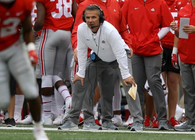 Urban Meyer watched the Buckeyes roll  to a 49-6 win in his return to the sideline.