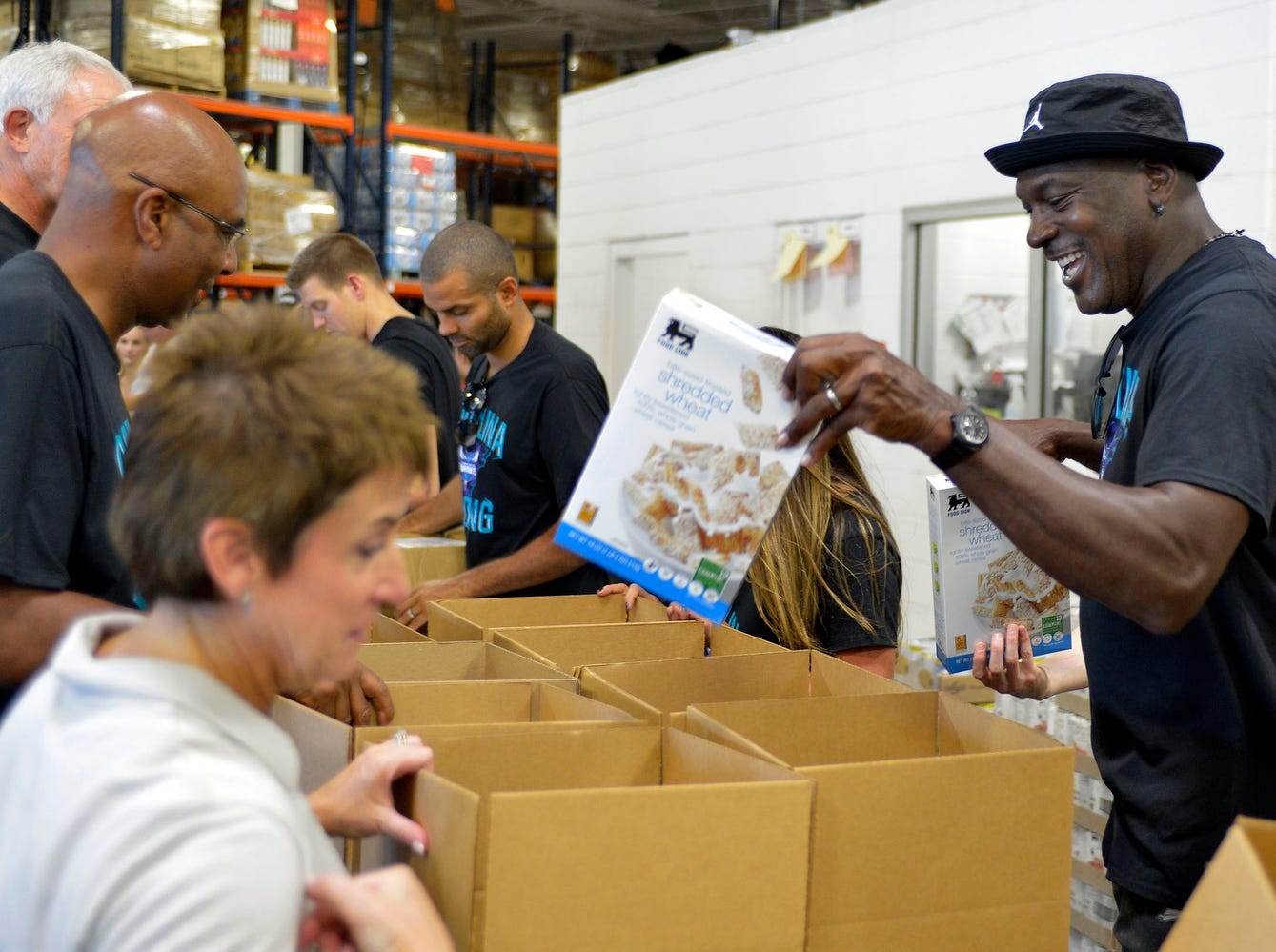 Charlotte Hornets owner Michael Jordan, right, loads boxes with goods for Hurricane Florence victims as he makes an appearance Friday, Sept. 21, 2018, at Second Harvest Food Bank of Metrolina in Charlotte, N.C. The Hornets NBA basketball team packed food boxes as part of hurricane relief efforts.