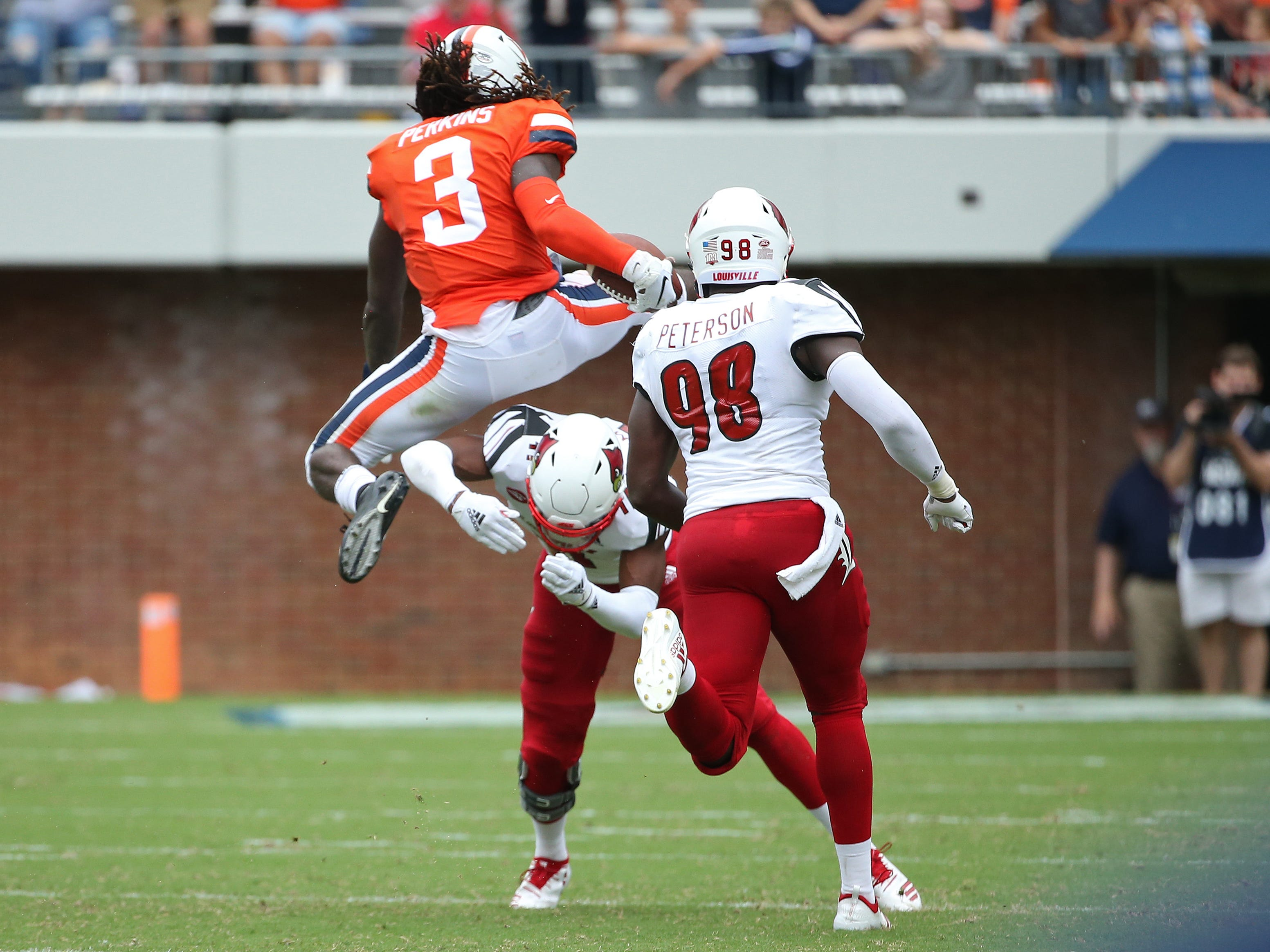 Virginia Cavaliers quarterback Bryce Perkins leaps over Louisville Cardinals safety Dee Smith while running with the ball in the third quarter at Scott Stadium.