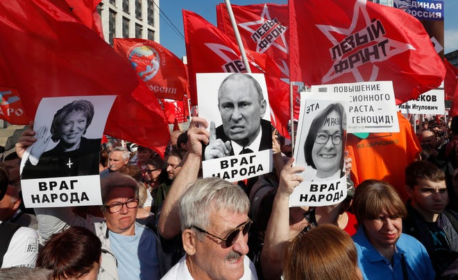 Supporters of Russian Communist party hold portrait of Russian Federation Council Chairman Valentina Matvienko (L), Russian President Vladimir Putin (C) and Head of the Russian Central Bank Elvira Nabiulina (R) with slogan read as 'Enemy of the people' during a protest rally against government's proposed pension reform plan in Moscow, Russia, on September 22, 2018.