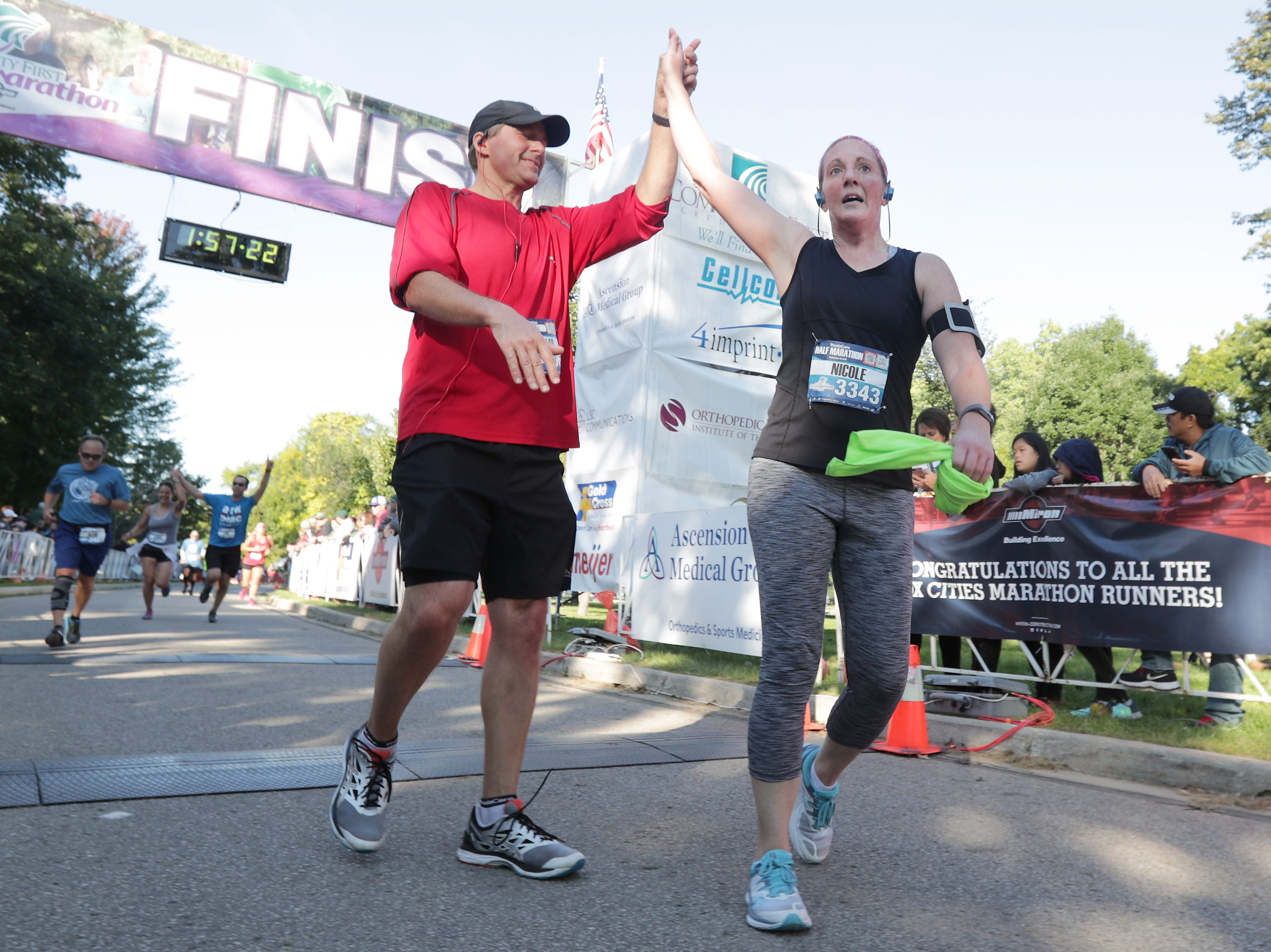Richard Frost and Nicole Esterling cross the finish line in the half marathon event during the 28th annual Community First Fox Cities Marathon on Sunday, September 23, 2018, in Neenah Wis. 